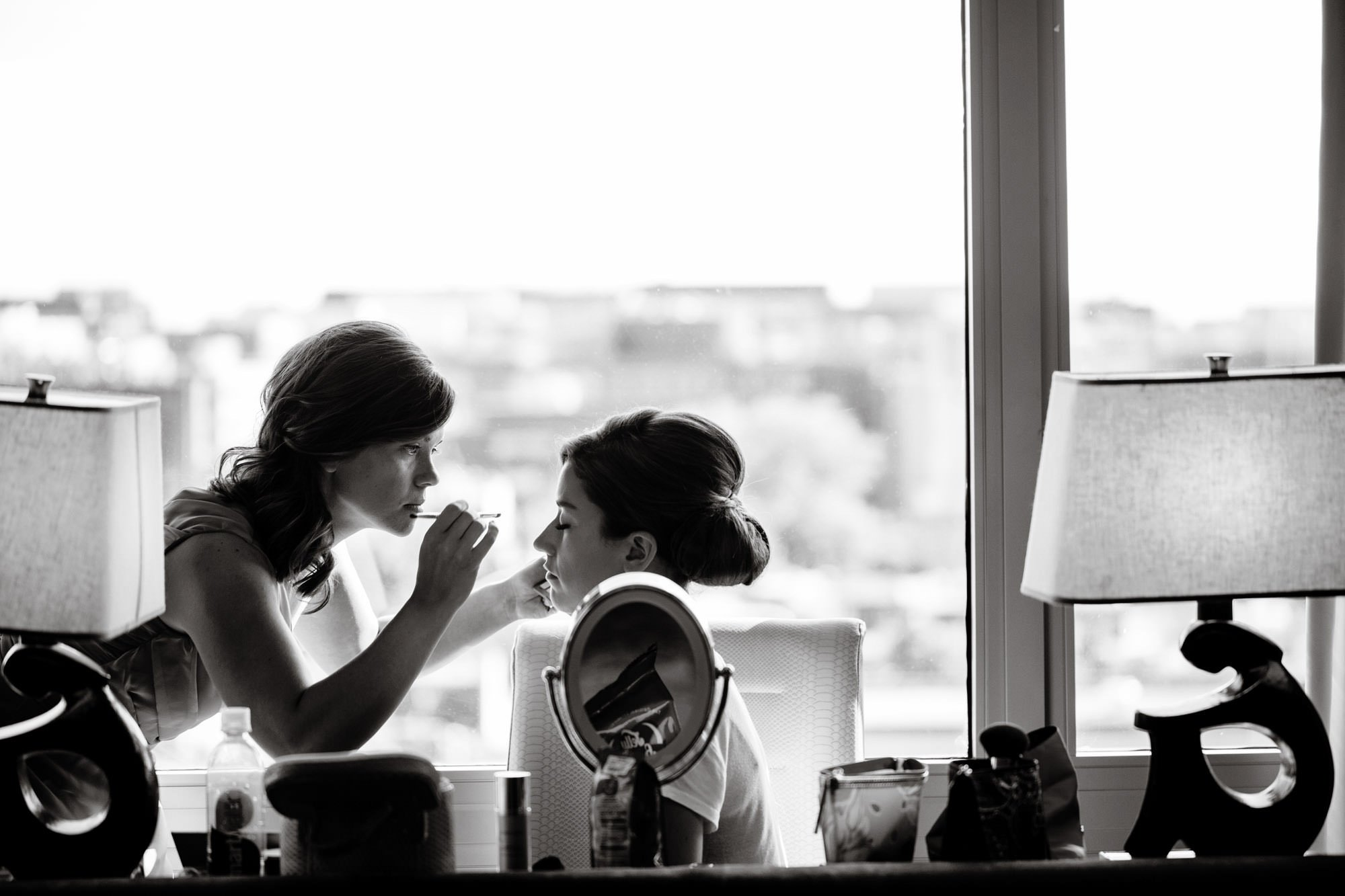 The bride gets her makeup done with help from her bridesmaid.