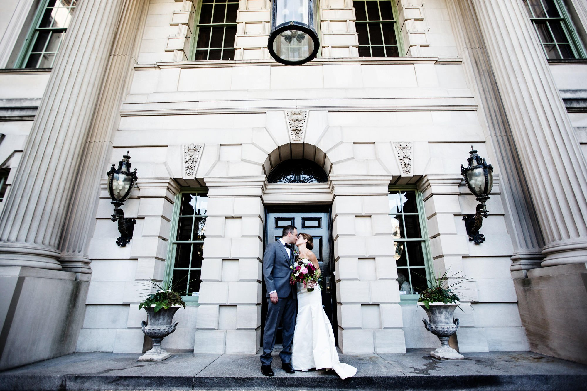 The bride and groom kiss at the entrance of Anderson House in Washington, DC.