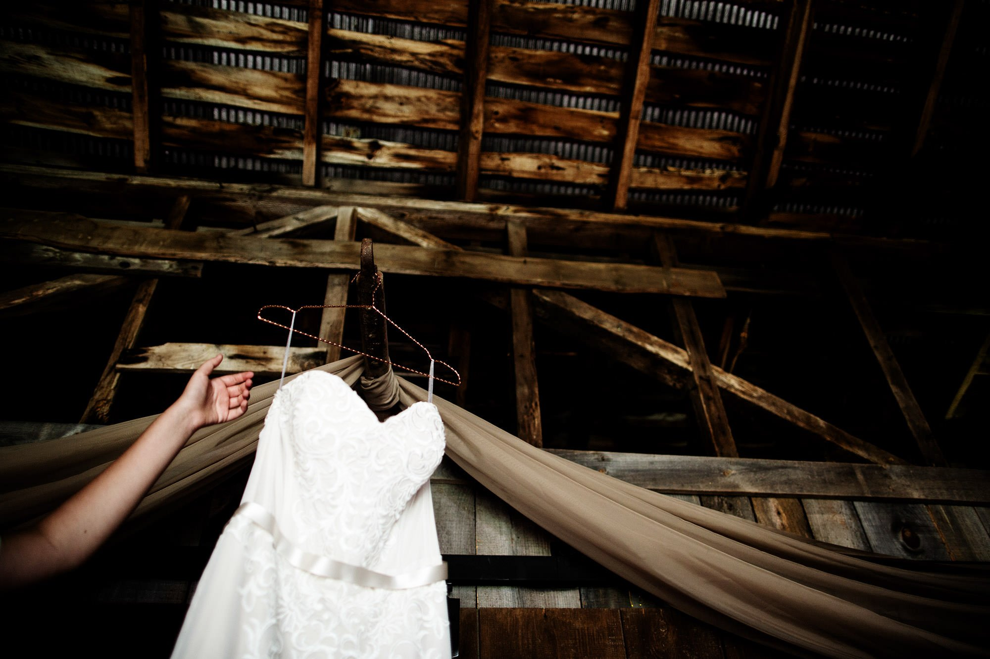 A detail of the bride's wedding gown in the barn of Bishop Farm.