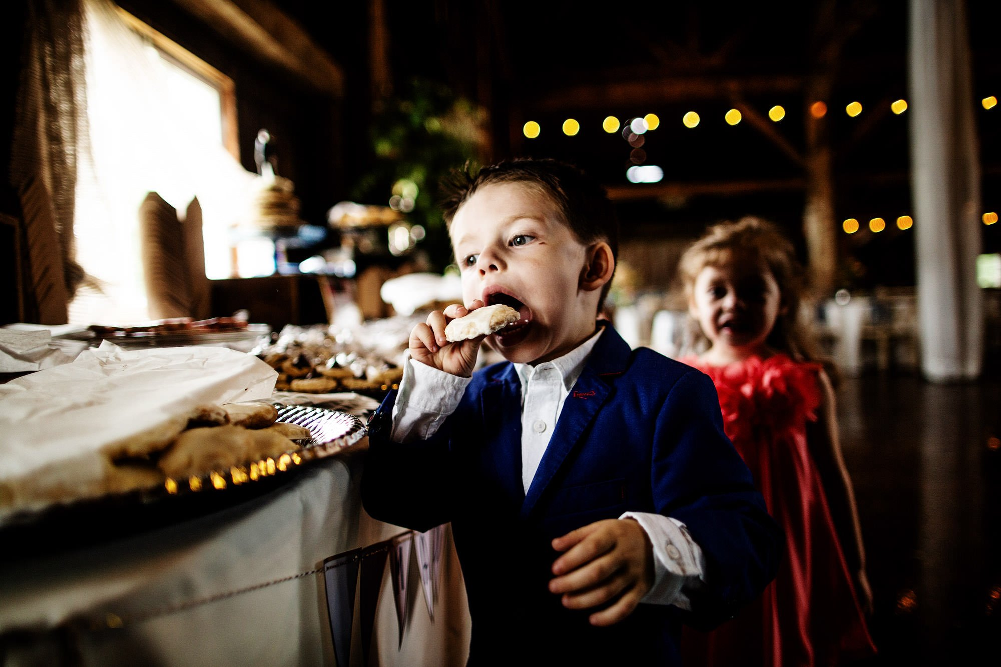 Kids eat cookies during cocktail hour at Bishop Farm.