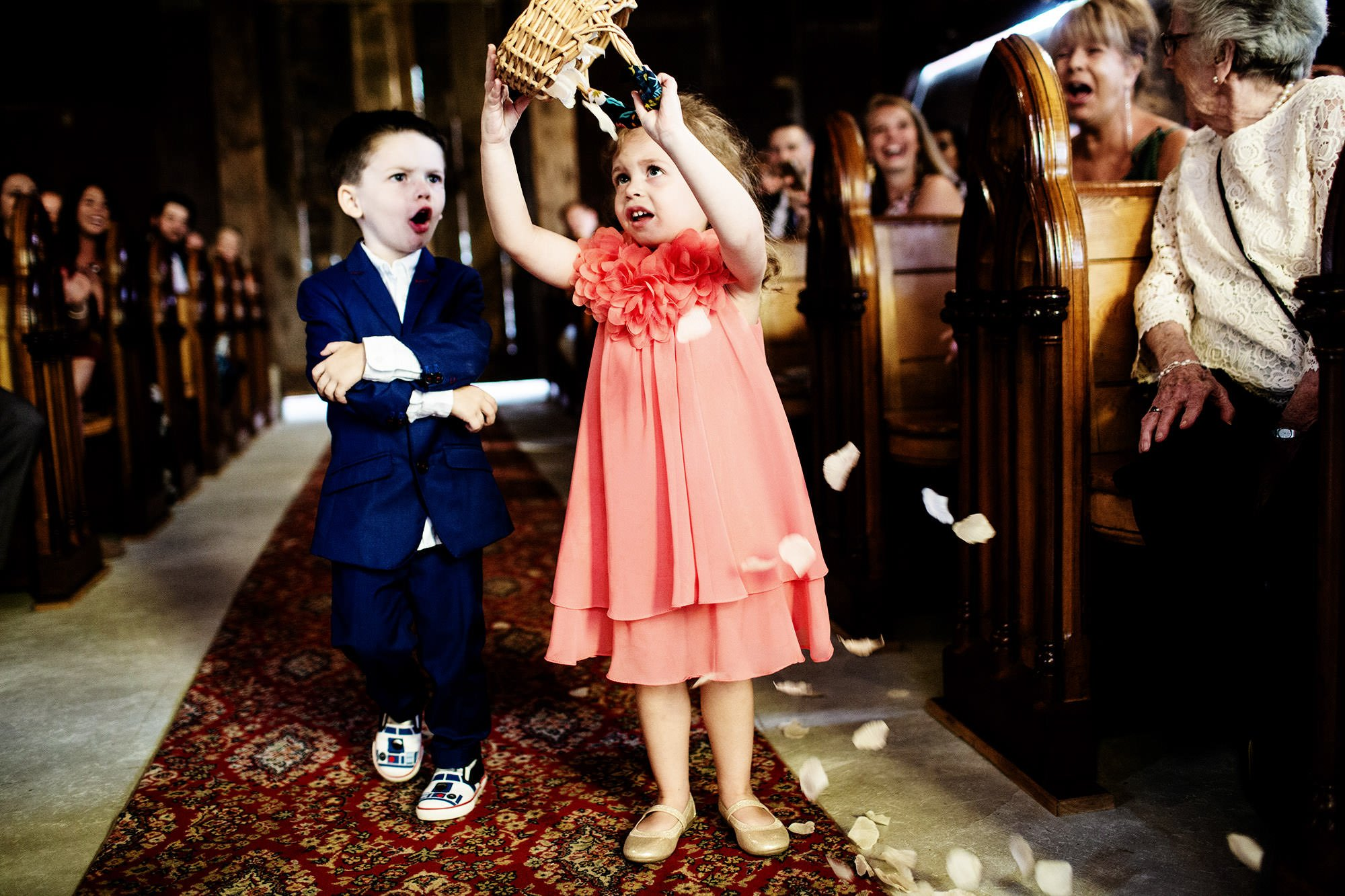 The flower girl unloads her basket in the aisle during the wedding ceremony at Bishop Farm.