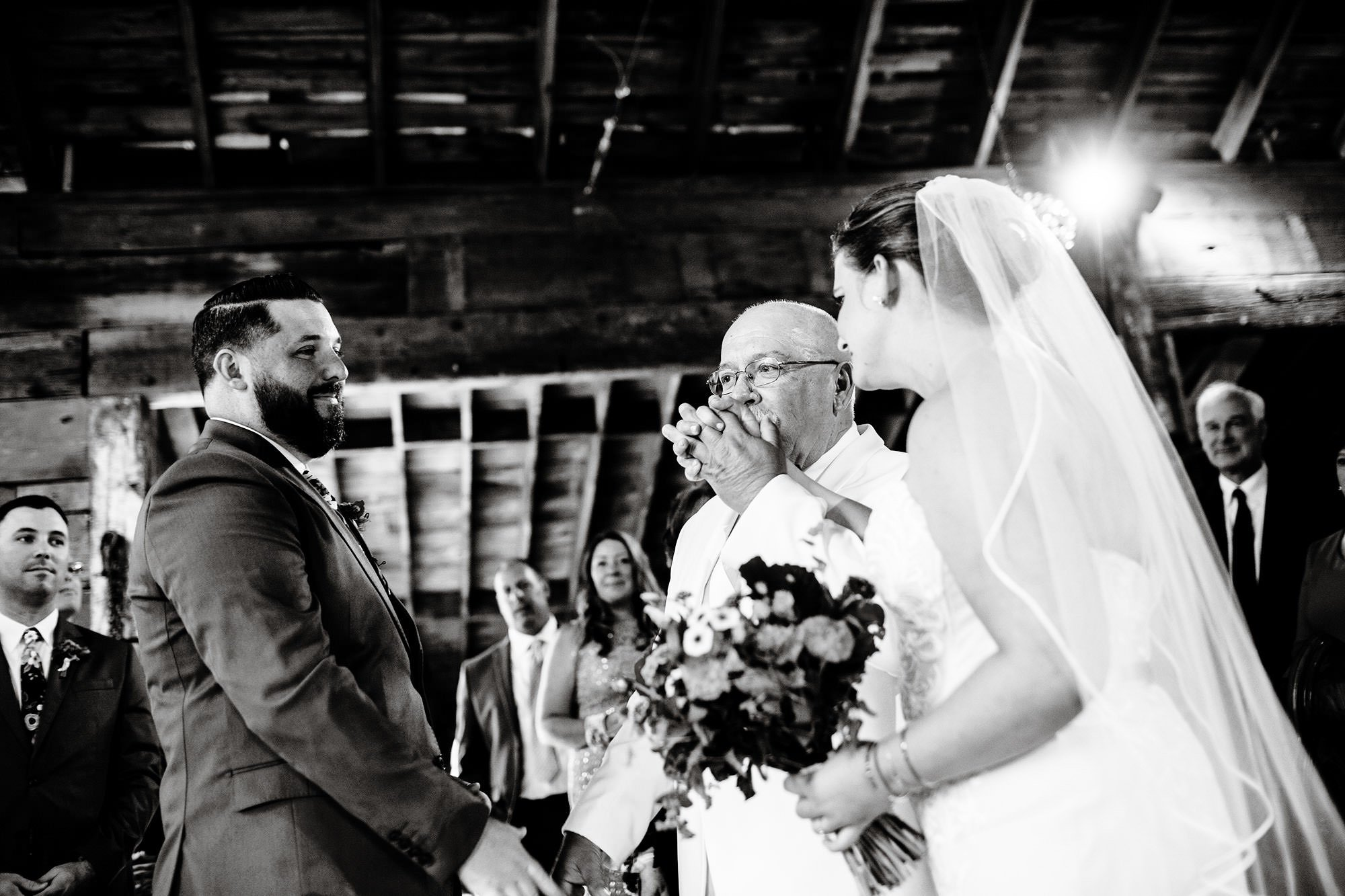 The father of the bride kisses his daughter's hand during the wedding ceremony at Bishop Farm.