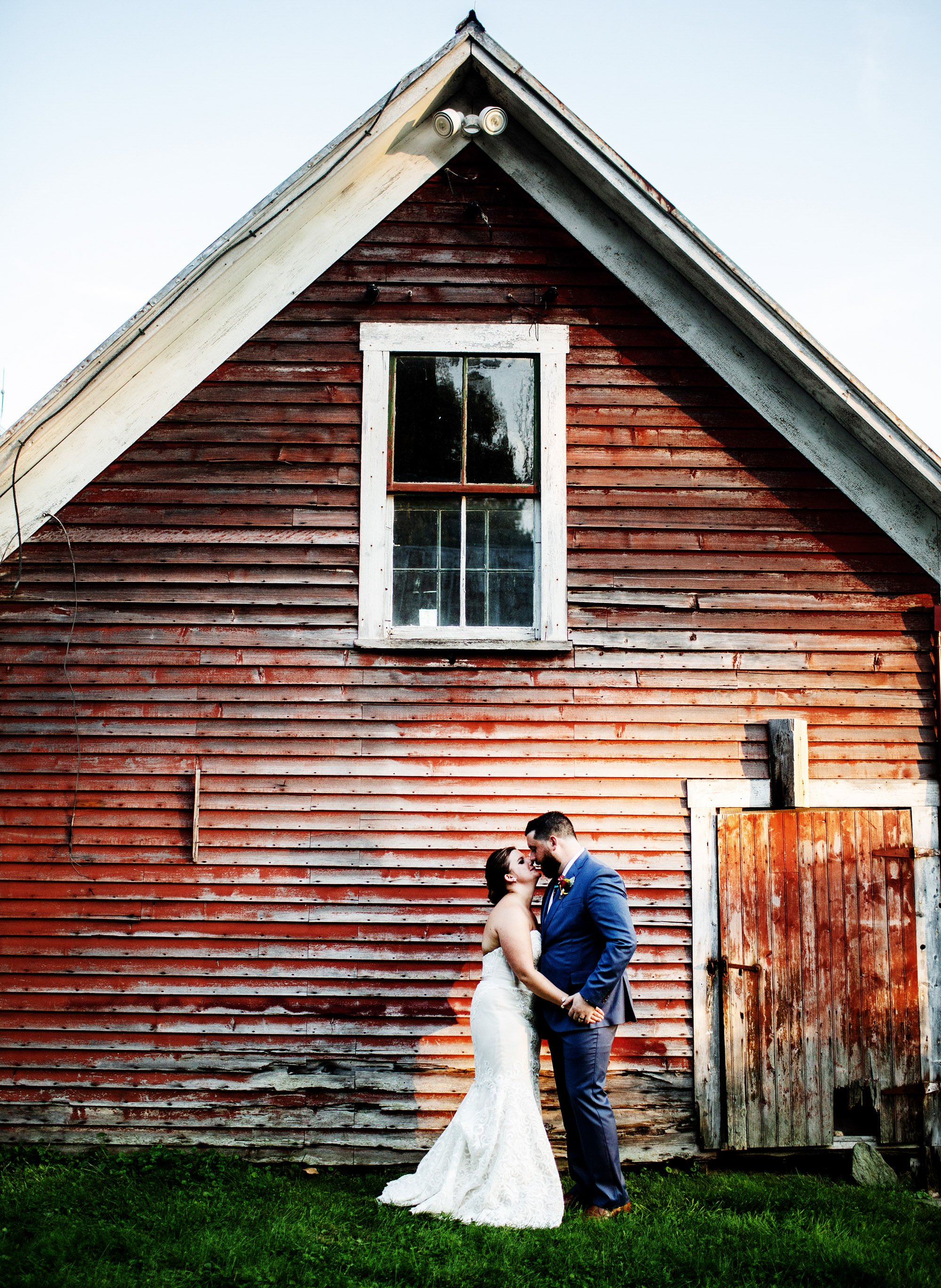 The bride and groom pose in front of a red barn on their Bishop Farm wedding day.