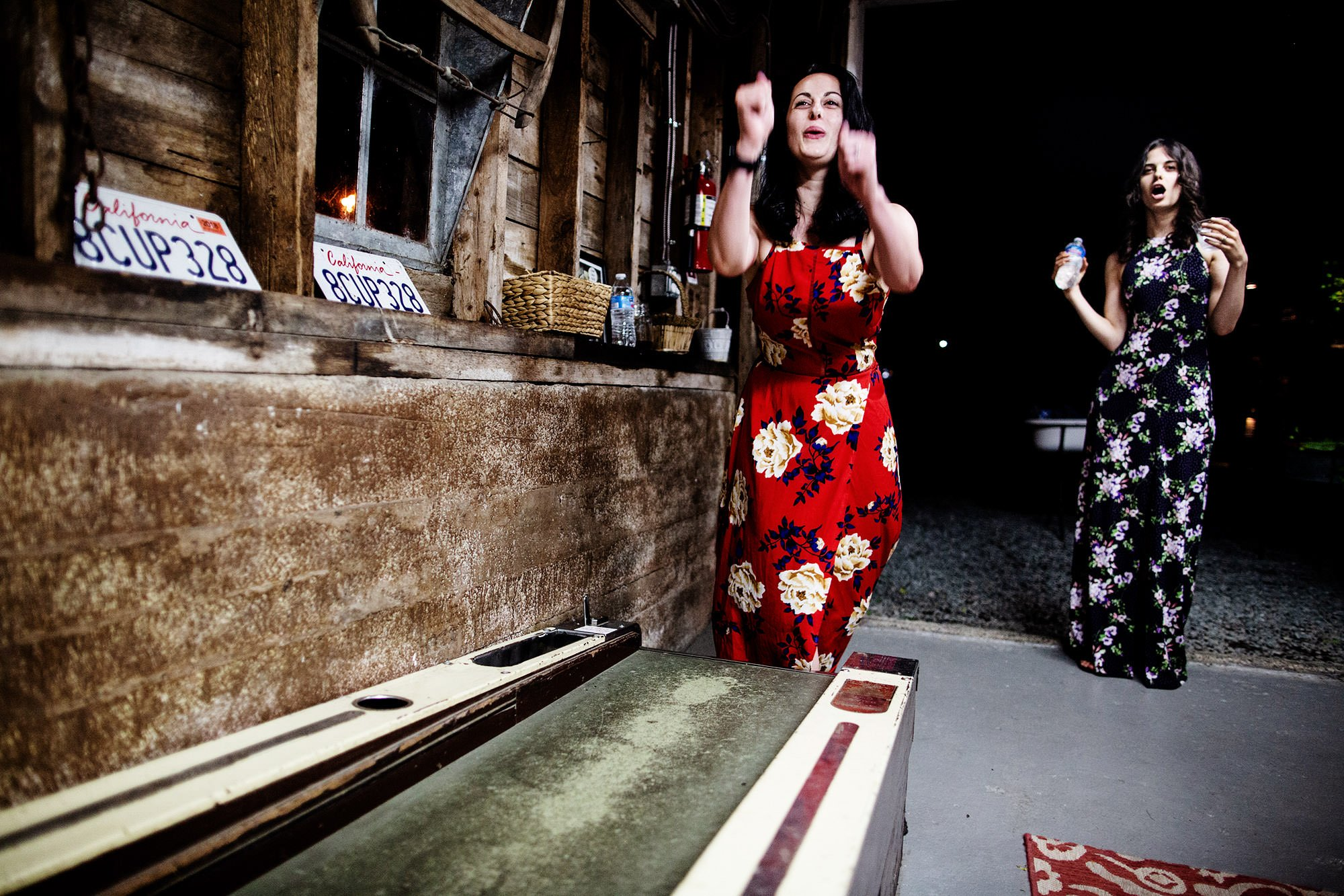 Guests play skee ball during the wedding reception at Bishop Farm.