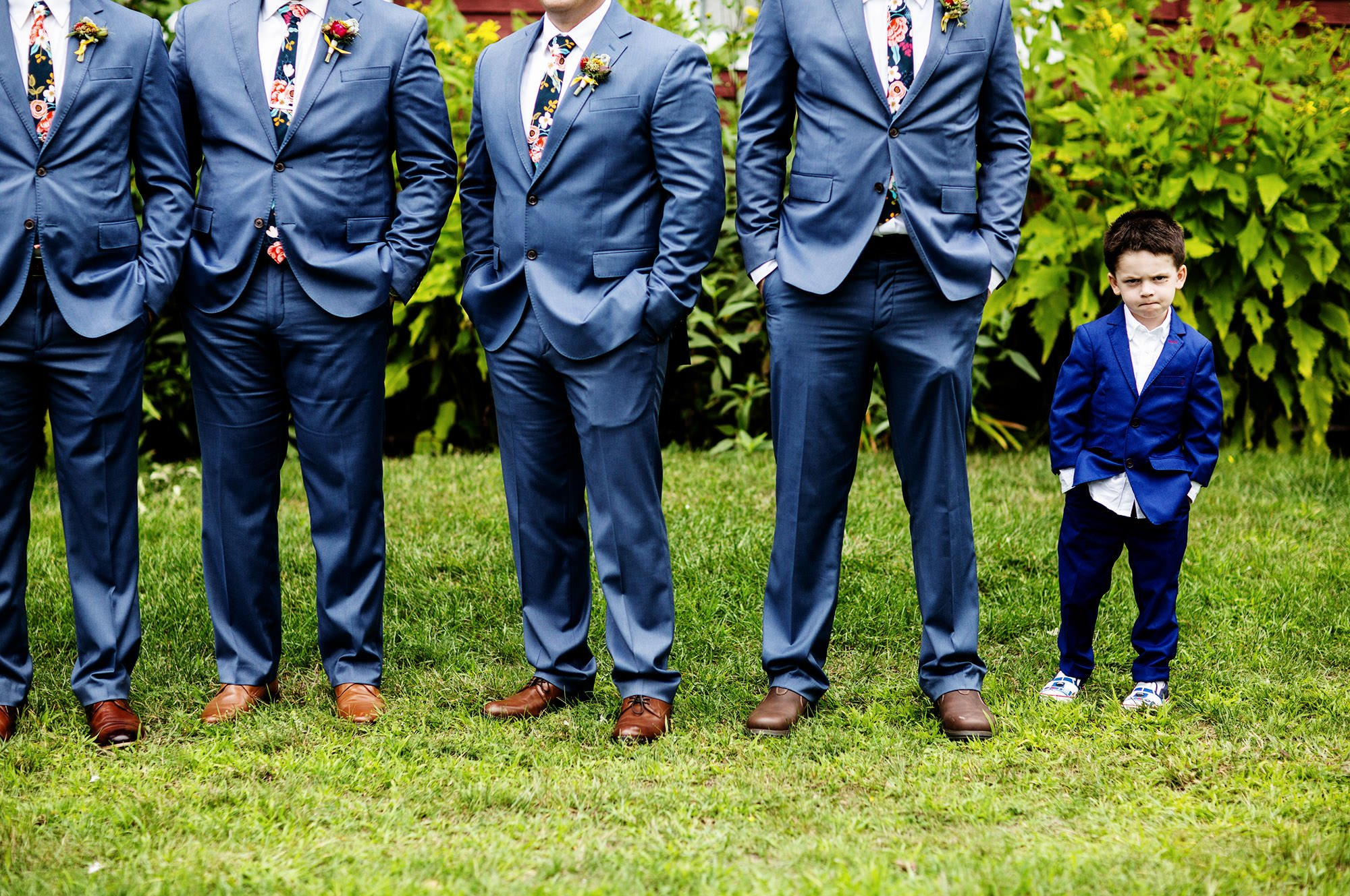 Groomsmen pose for a portrait on the Bishop Farm wedding day.