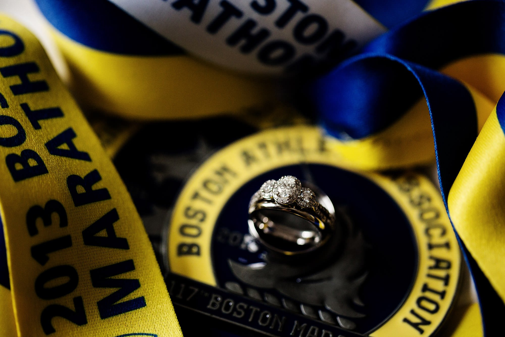 A ring detail next to Boston Marathon medals.