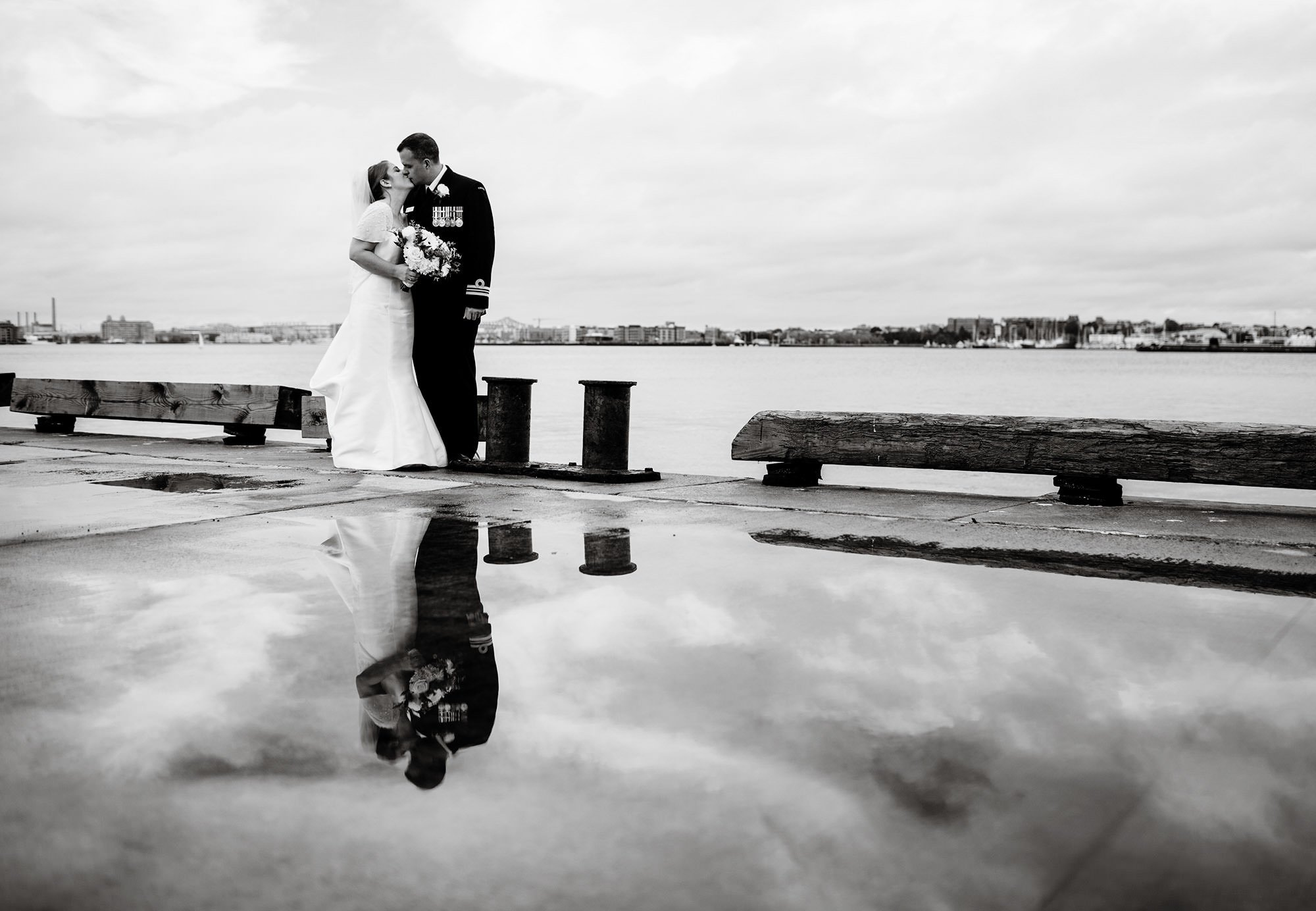 The bride and groom kiss along the dock outside of the Exchange Conference Center wedding in Boston.
