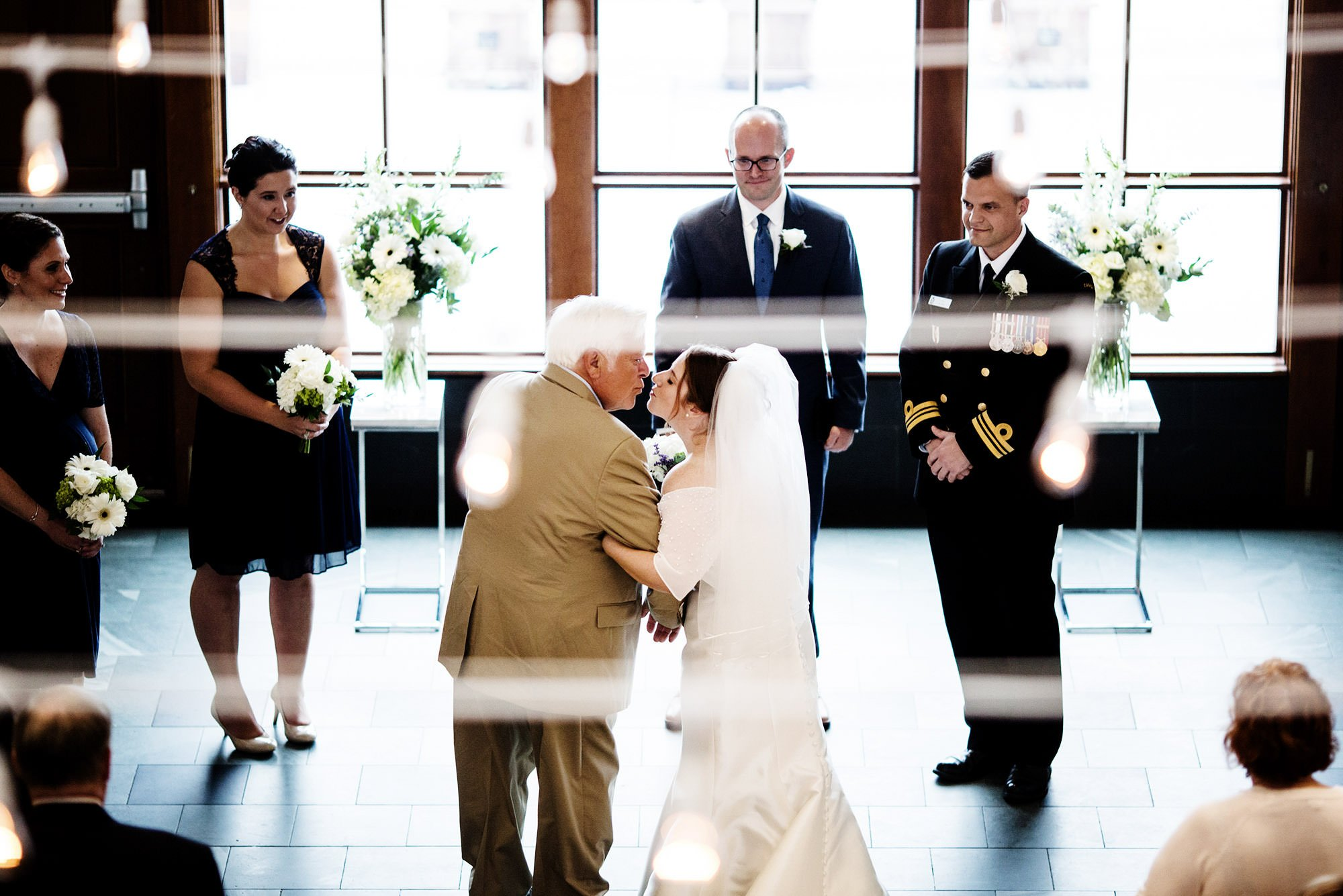 The bride kisses her father during the wedding ceremony at Exchange Boston.