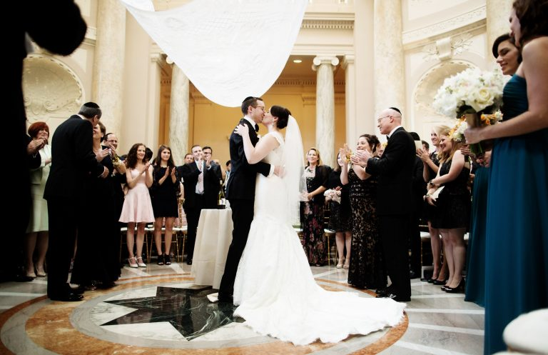 The bride and groom kiss under the chuppah during the ceremony of their Carnegie Institution for Science Wedding.