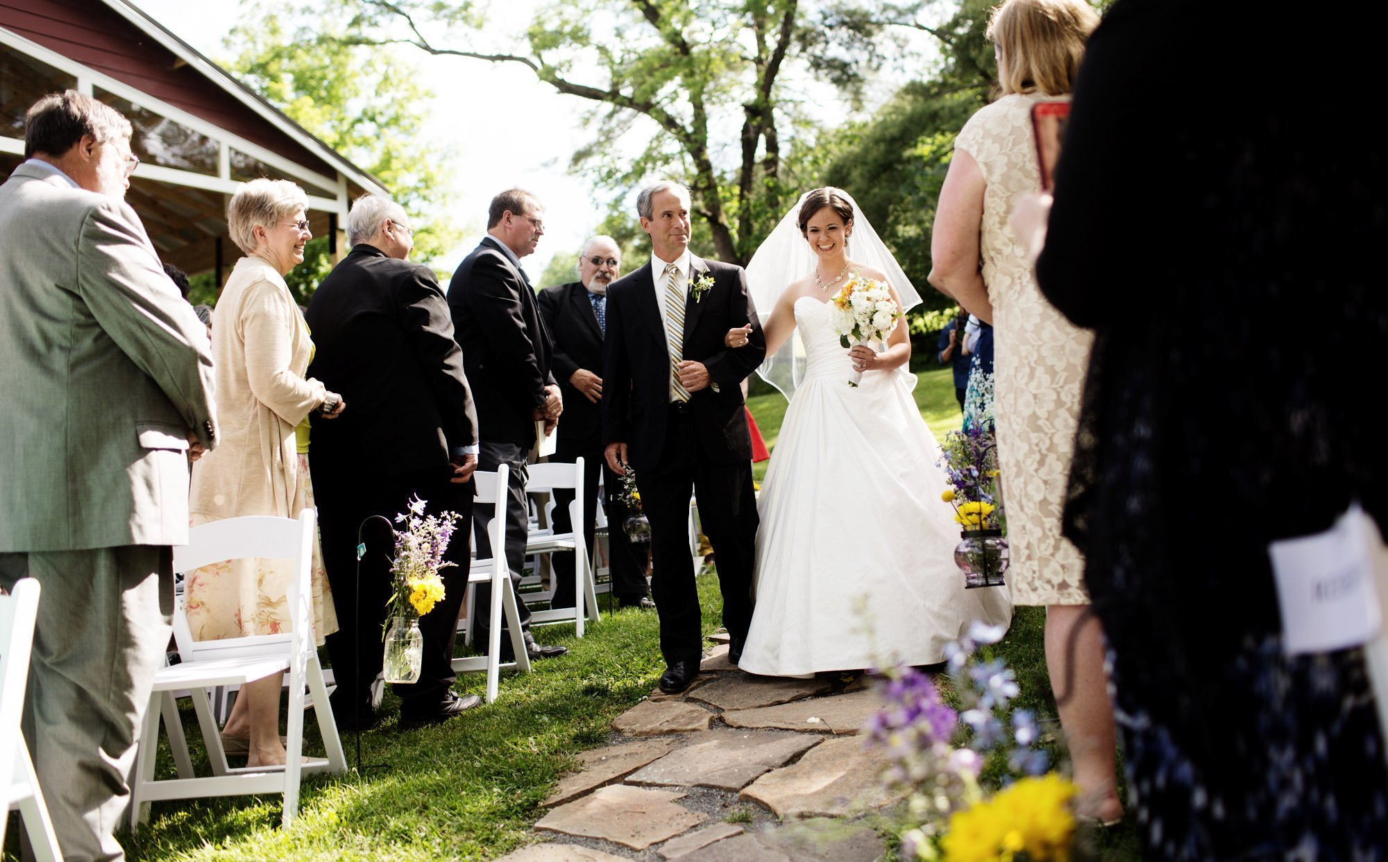 The bride is escorted down the aisle during her wedding at Chanteclaire Farm.