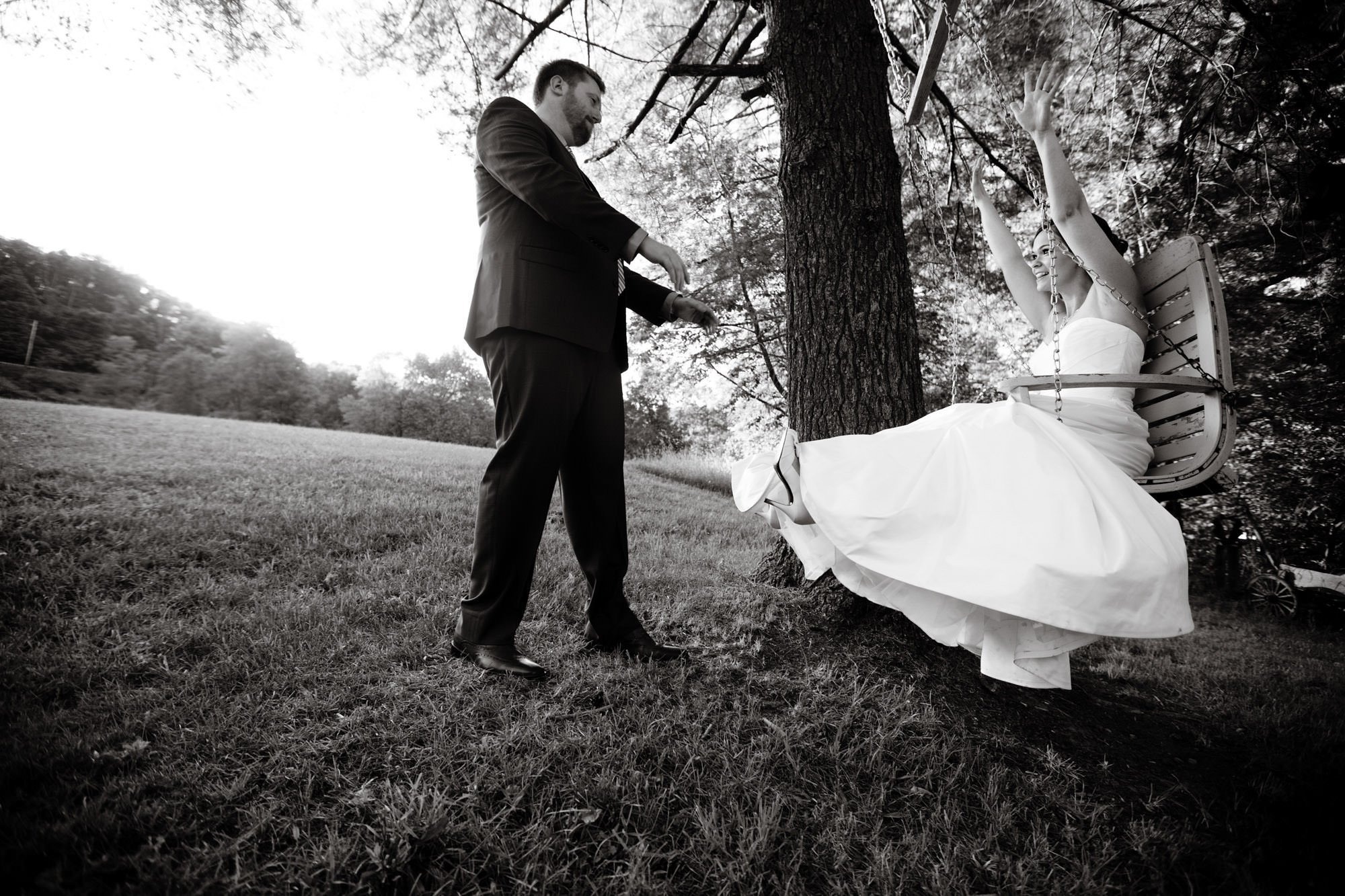 The pushes his bride on the swing during cocktail hour of their Chanteclaire Farm Wedding.