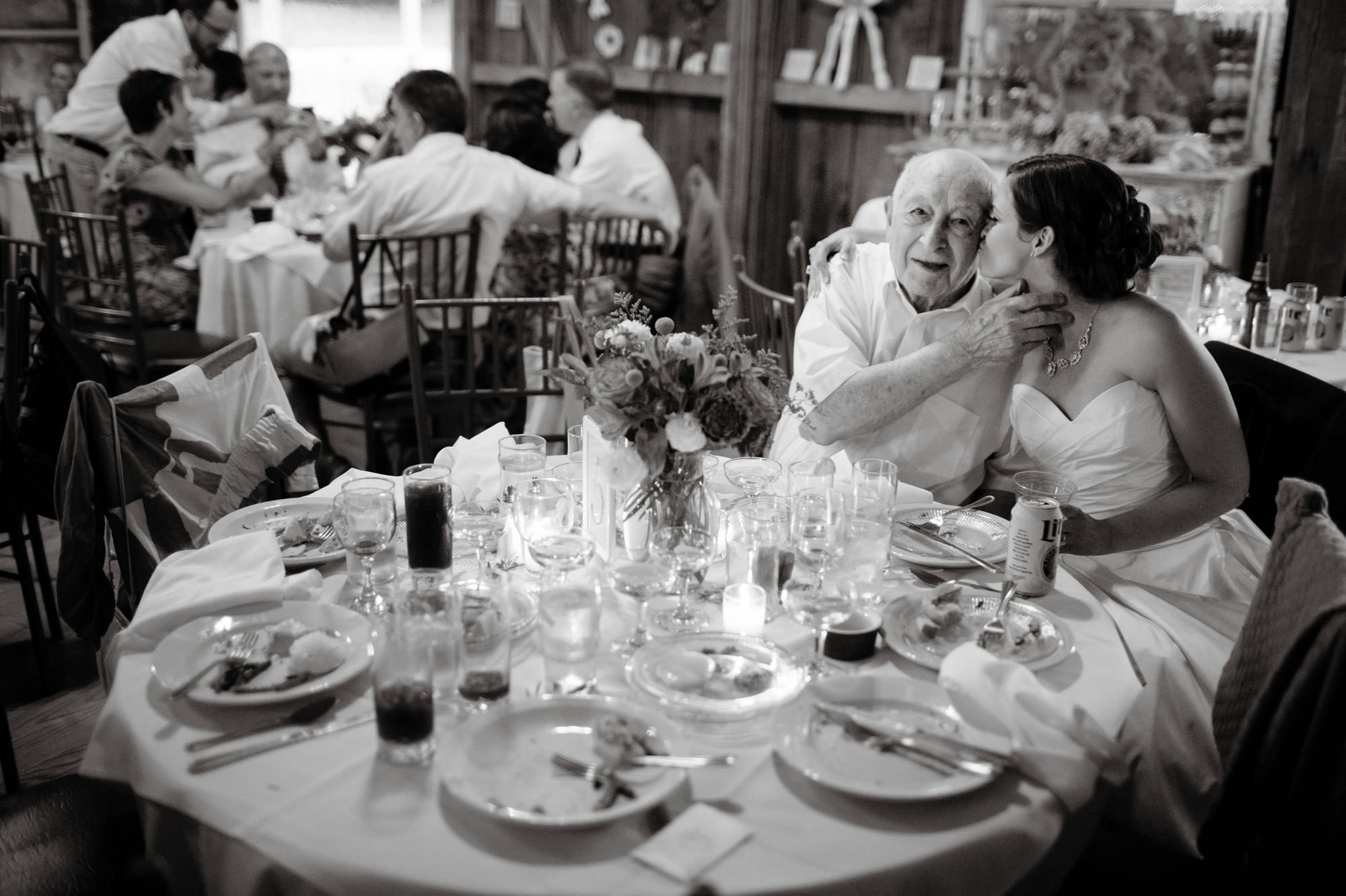 The bride kisses her grandfather during her Chanteclaire Farm Wedding.