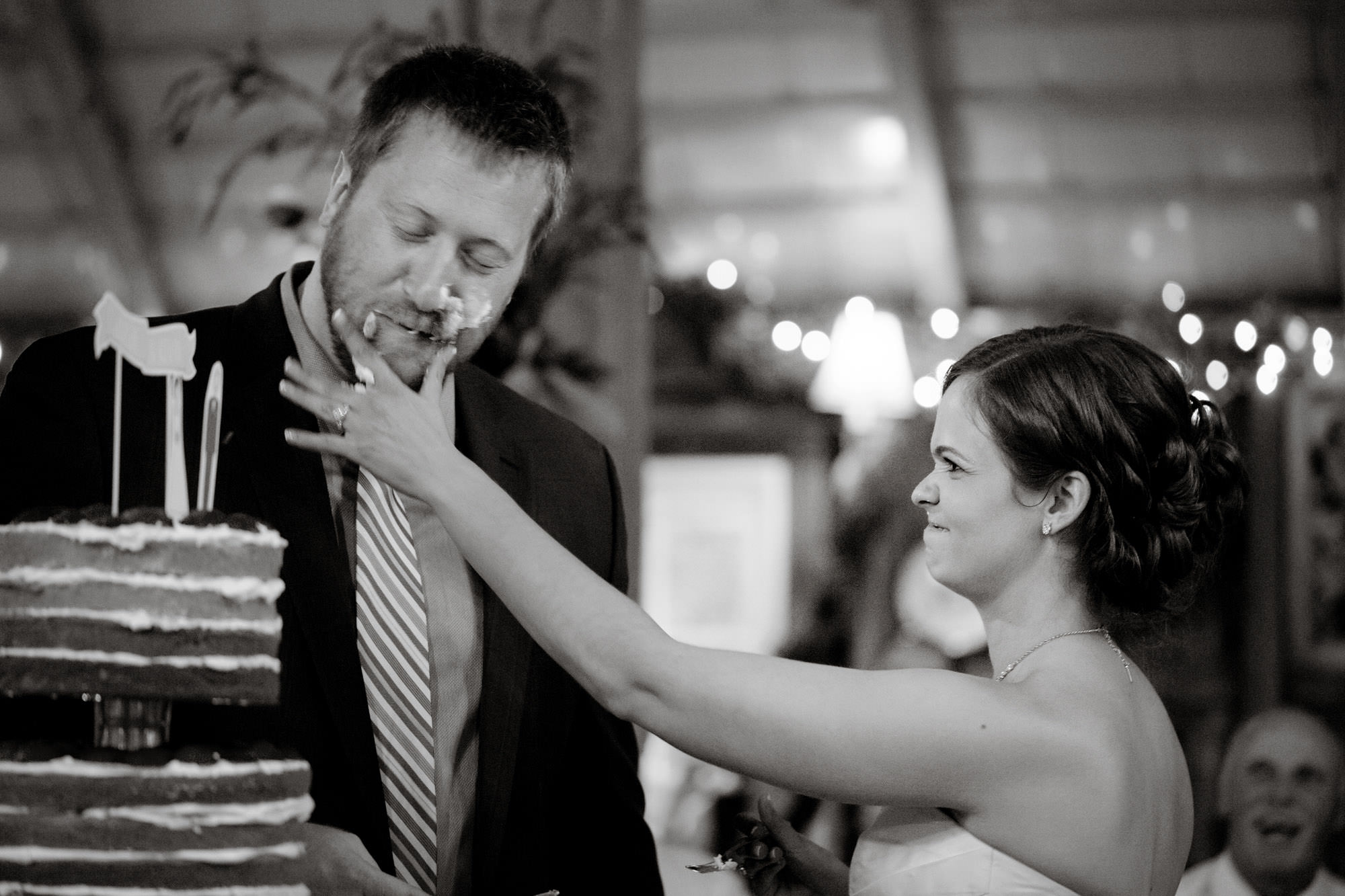 The bride and groom cut the cake during their Chanteclaire Farm Wedding.