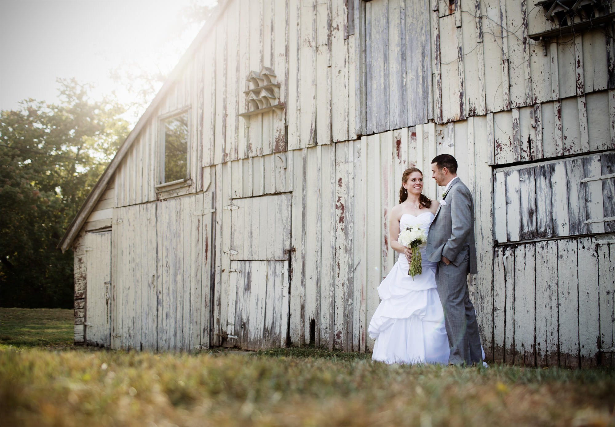 The bride and groom pose beside a barn during their Comus Inn wedding.