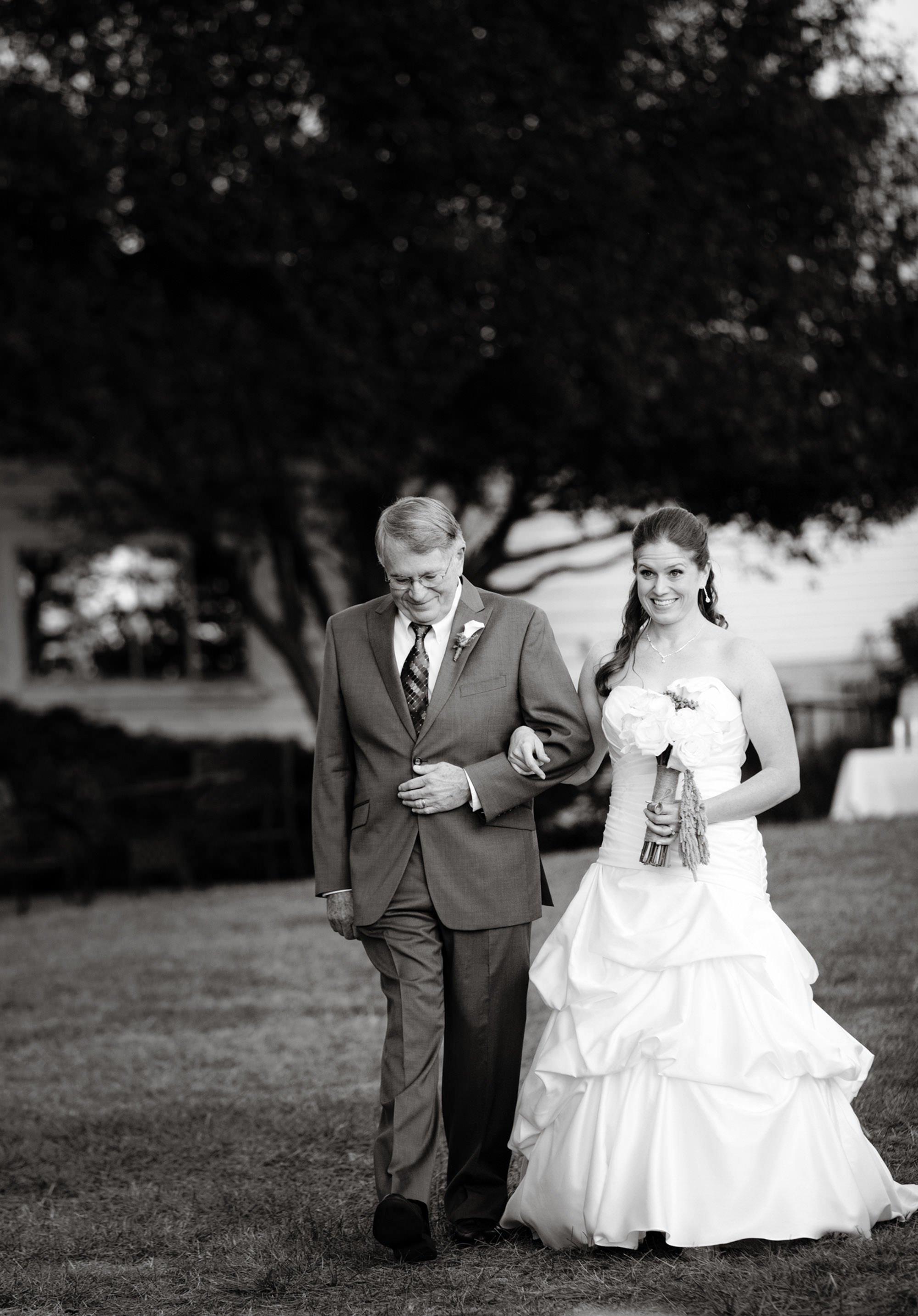 The bride is escorted by her father during the wedding ceremony at Comus Inn.