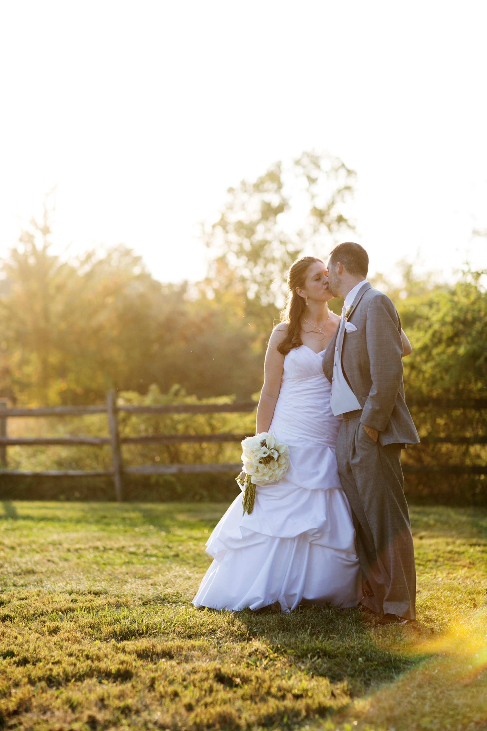 The couple kisses during sunset on their Comus Inn wedding day.