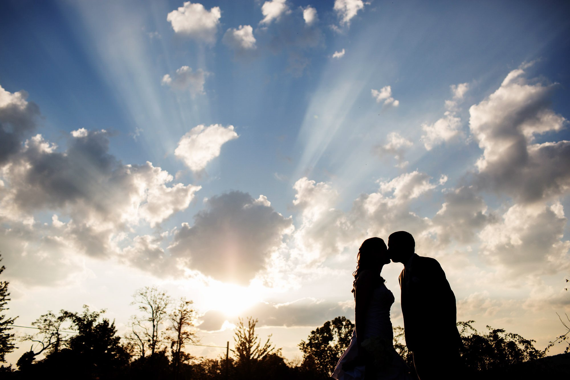 The bride and groom kiss at sunset during the reception of their Comus Inn wedding in Dickerson, MD.