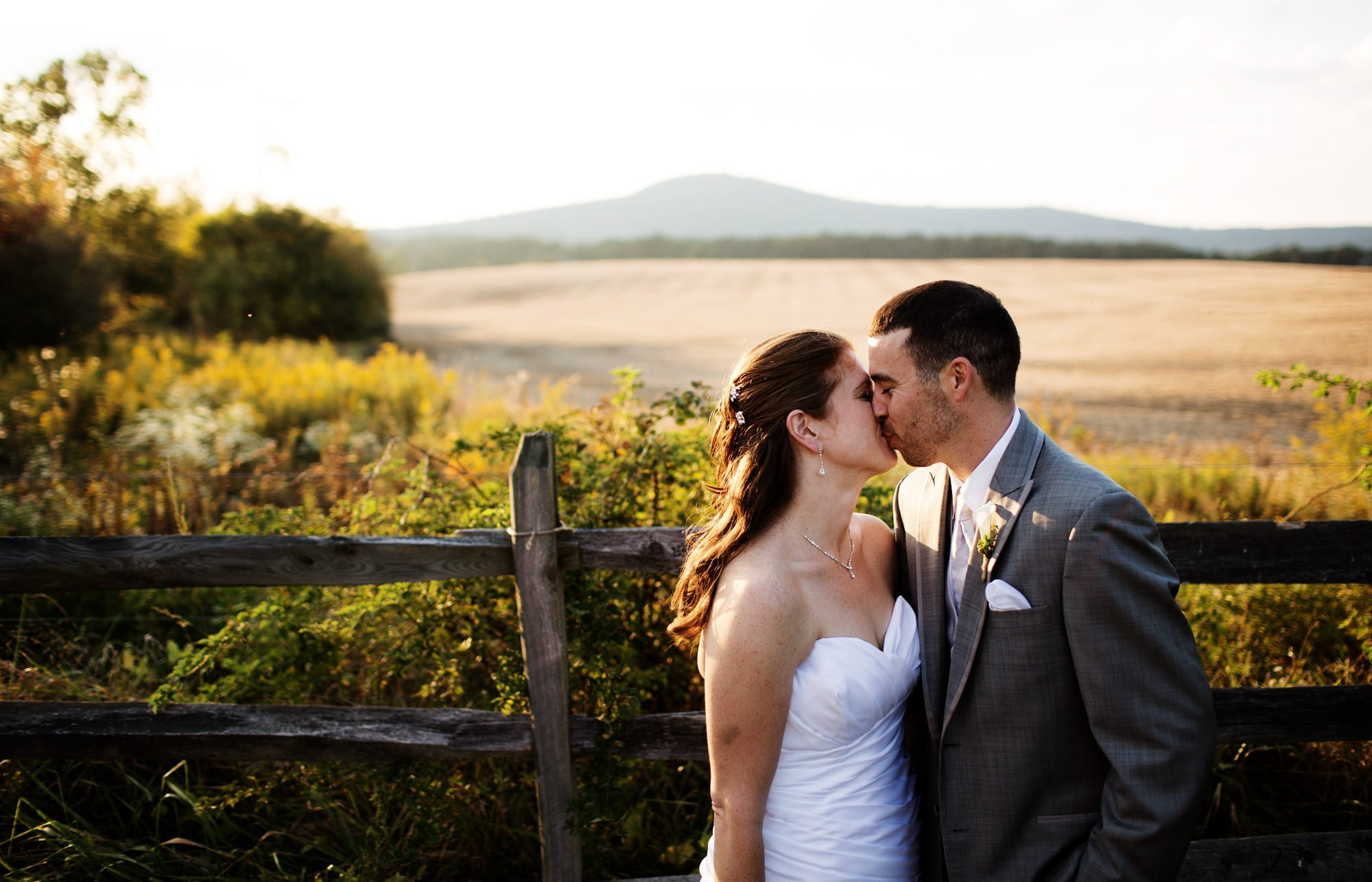 The couple kisses with the Sugarloaf Mountains in the distance during their Comus Inn wedding.