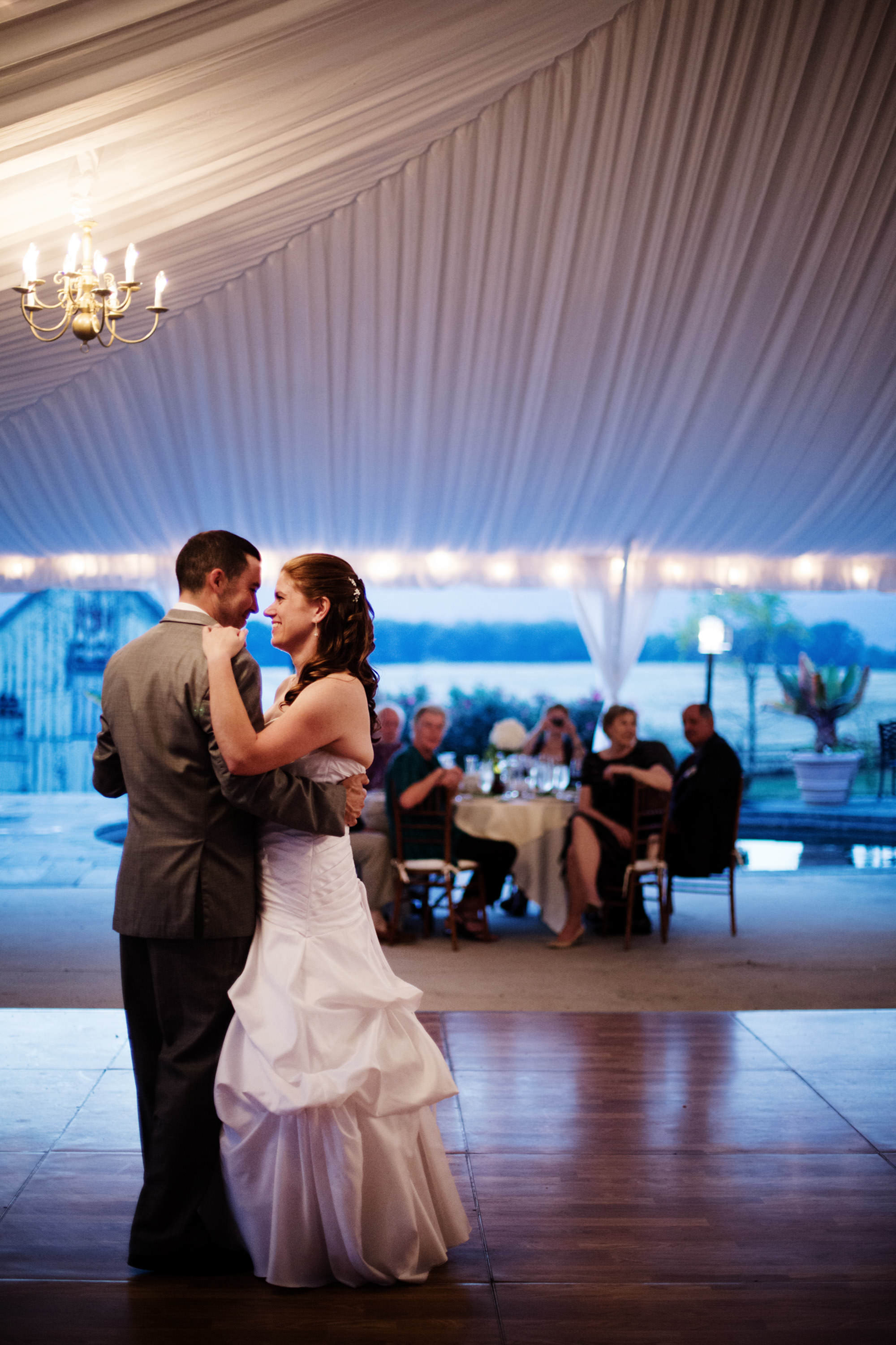 The couple enjoys their first dance in the tented reception of their Comus Inn wedding.