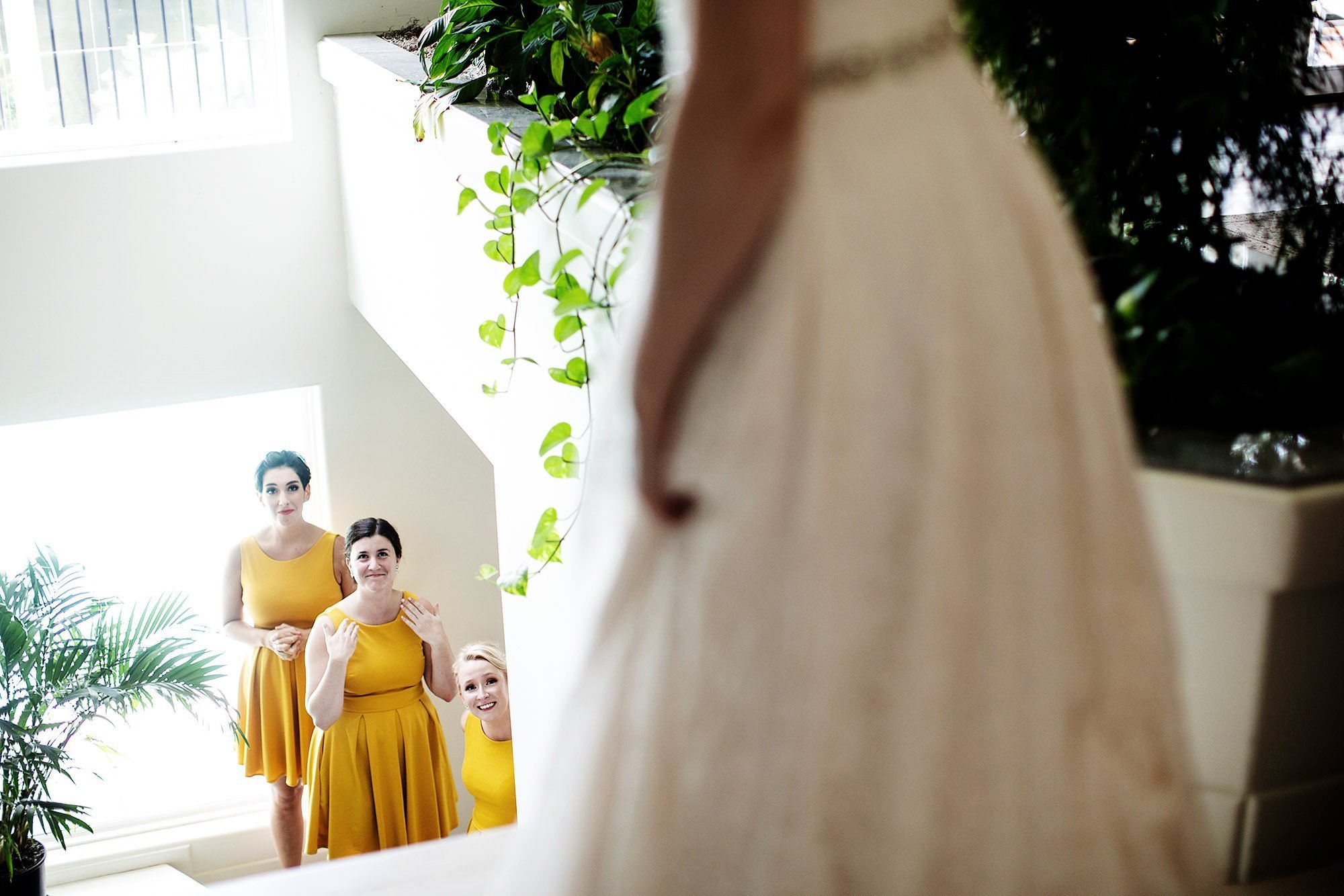 New Hampshire Backyard Wedding  I  Bridesmaids watch as the bride walks down the stairs before the outdoor ceremony.