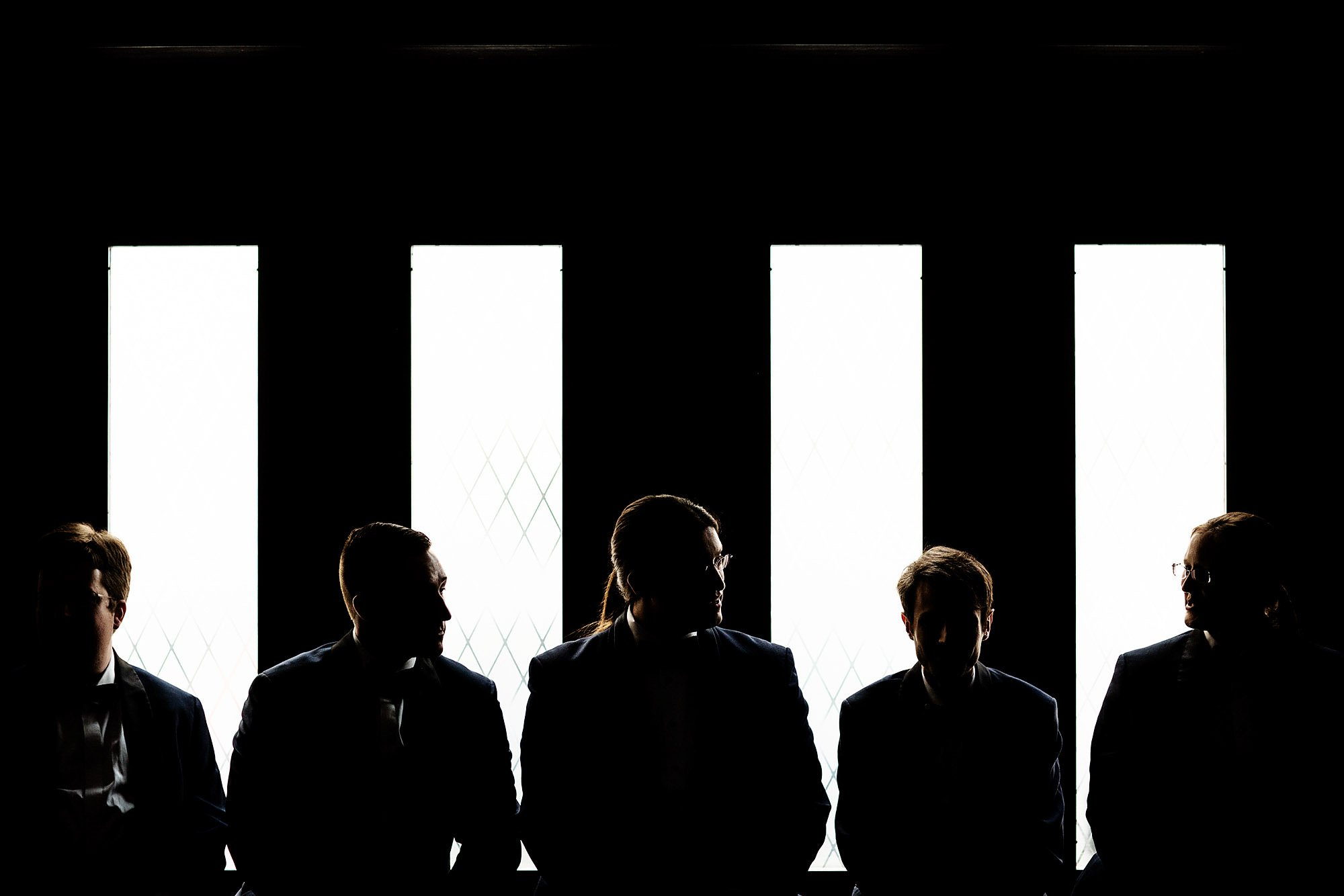 The groom and groomsmen sit in the lobby prior to the Courtyard Boston Downtown Wedding.
