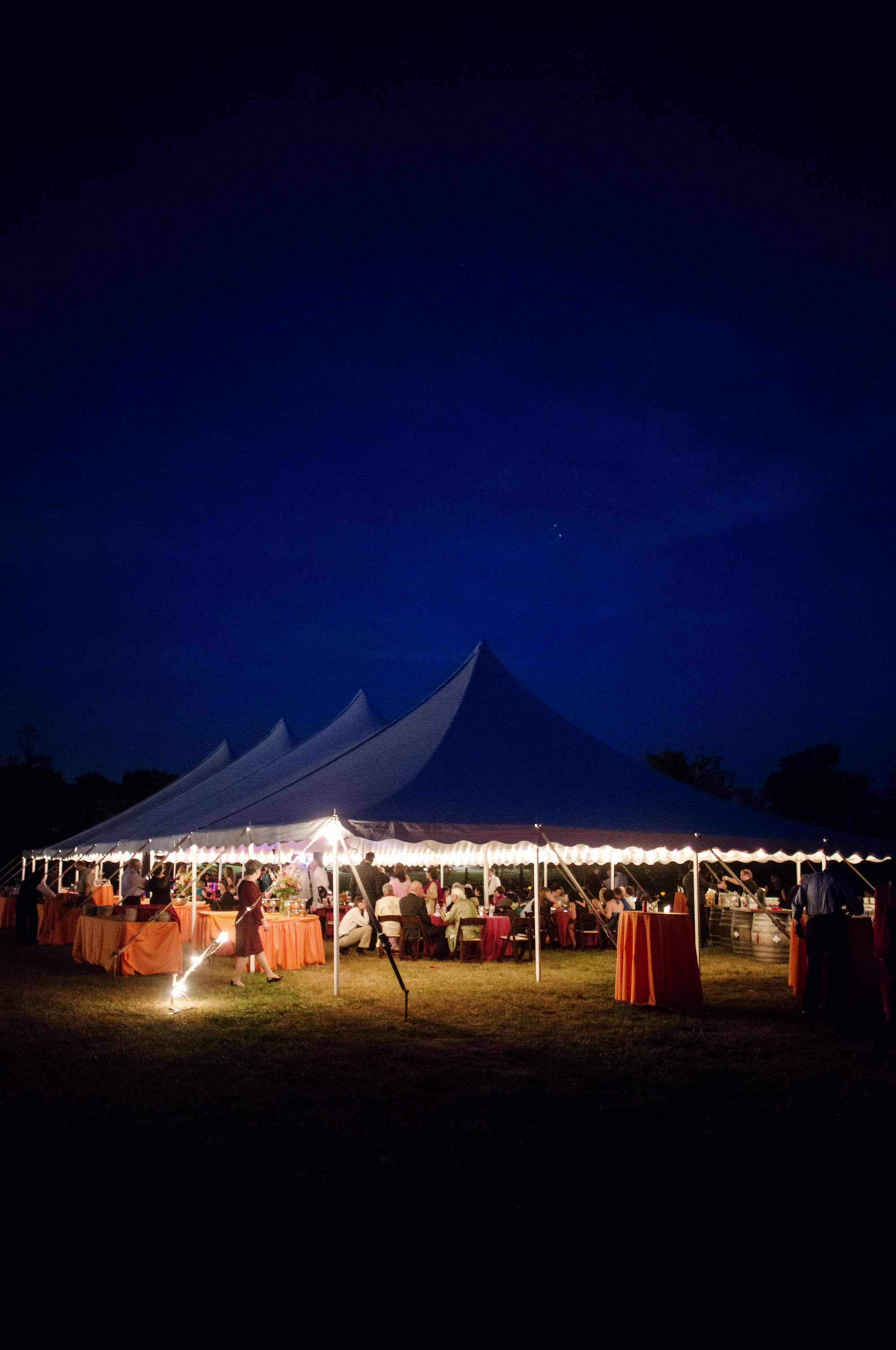 The sun sets on the tented reception of this Doukenie Winery wedding.