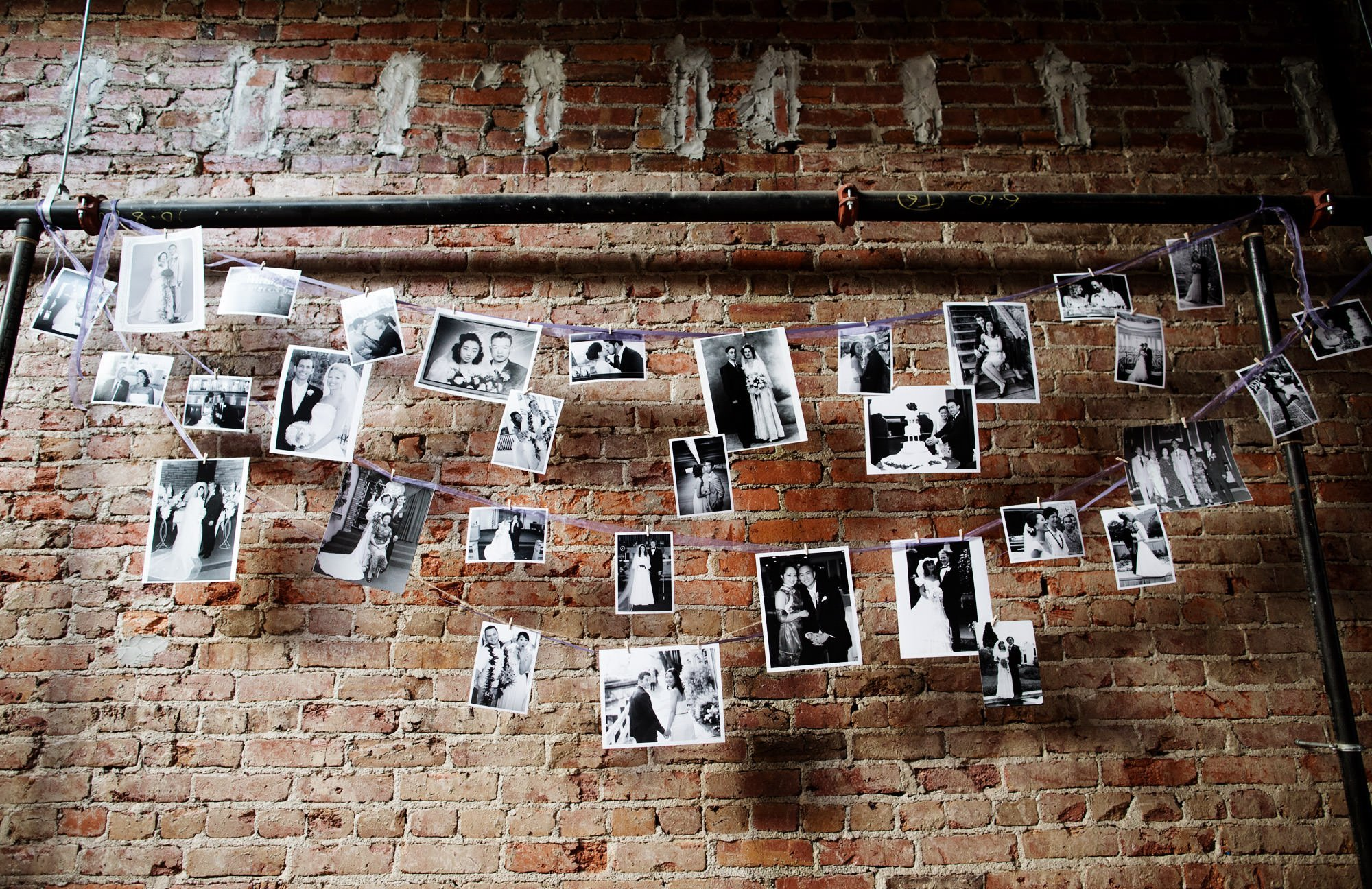 Photographs are hung against a brick wall during this Epic Yoga Studio wedding.