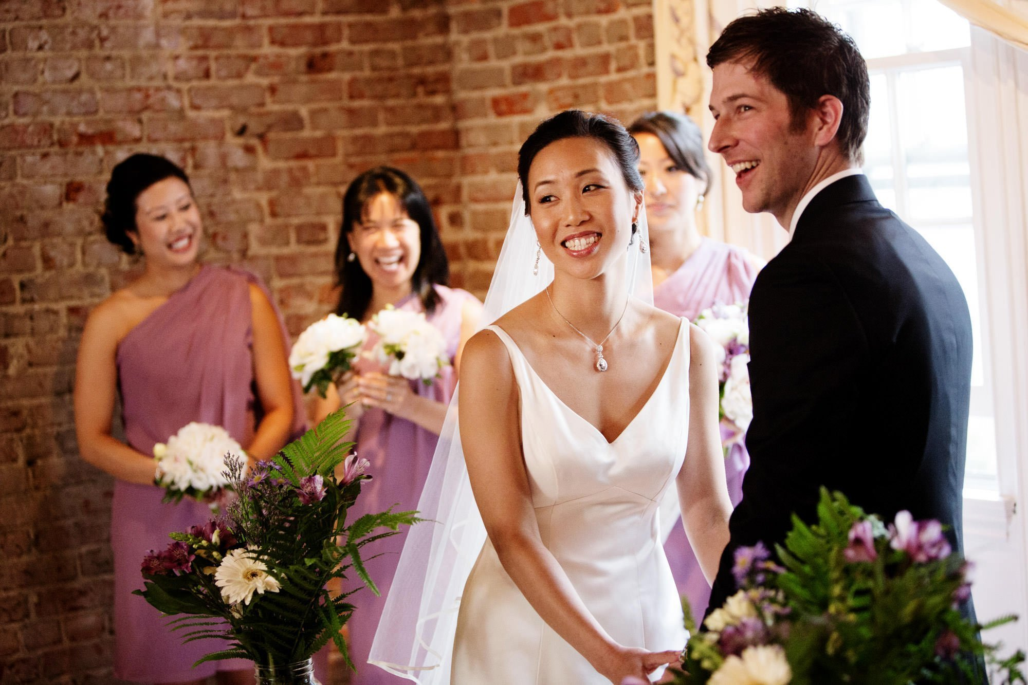 The couple laughs during their wedding ceremony at Epic Yoga Studio.