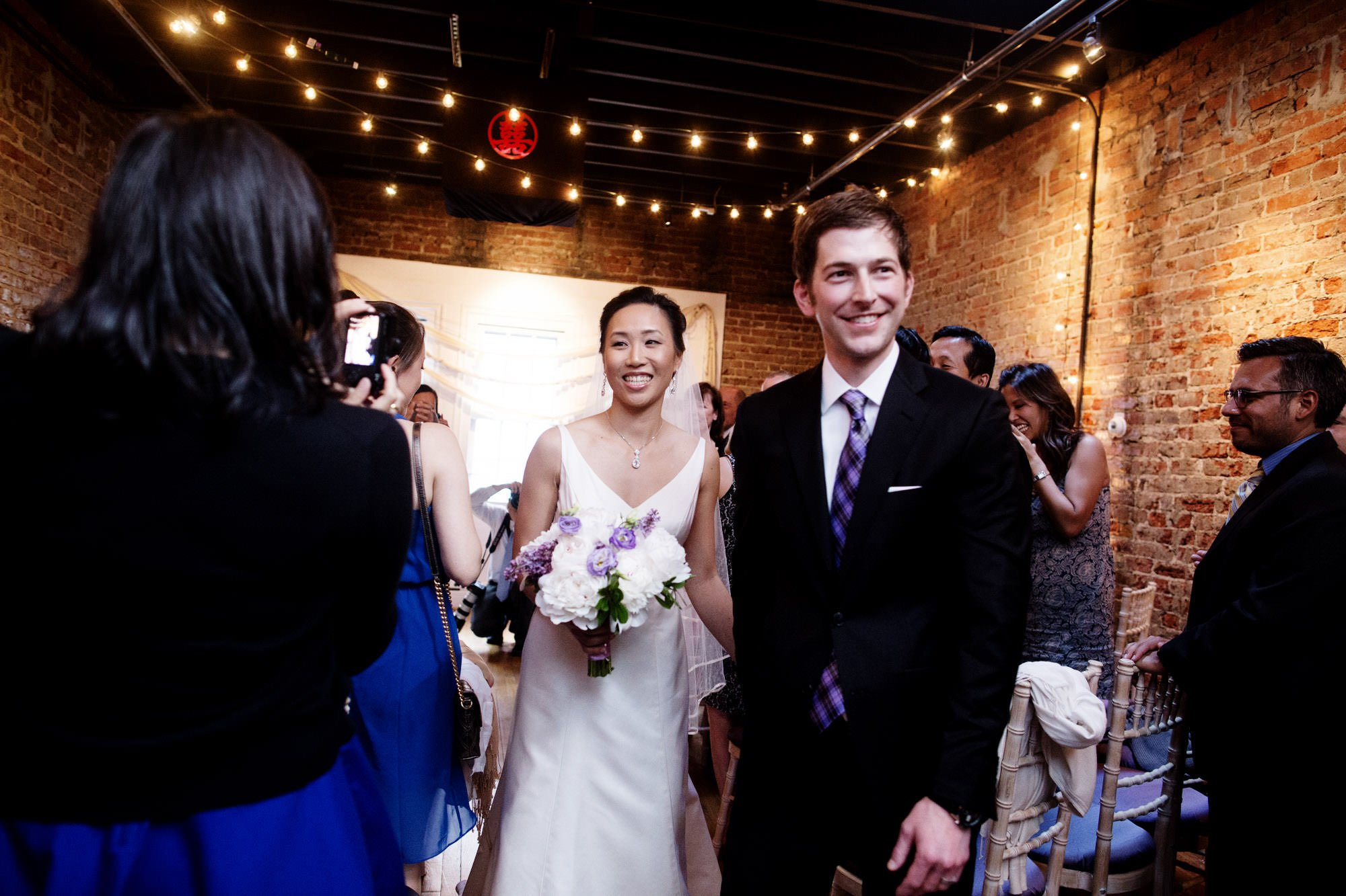 The bride and groom walk down the aisle following their wedding ceremony at Epic Yoga Studio.