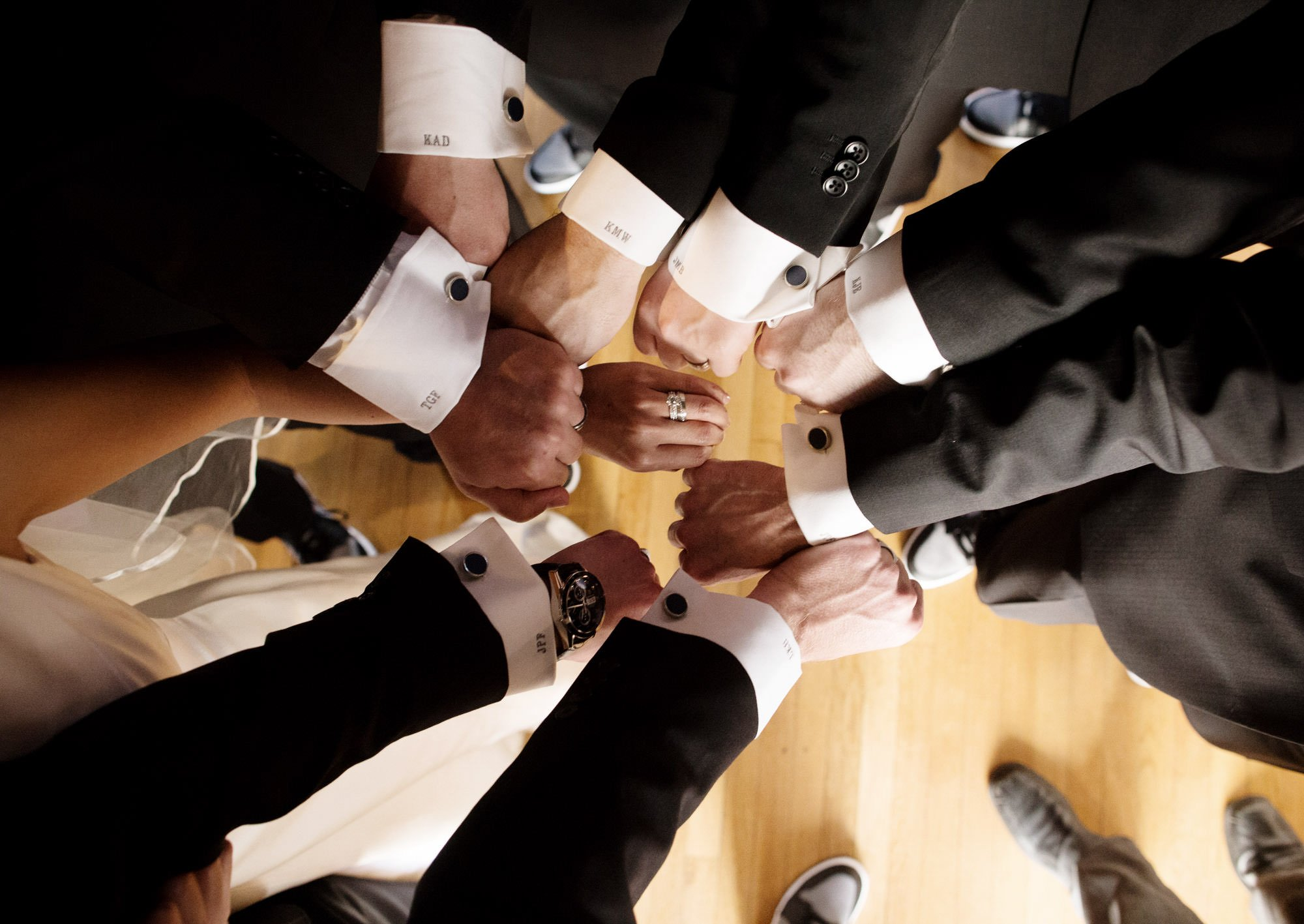 Groomsmen show off their cufflinks.