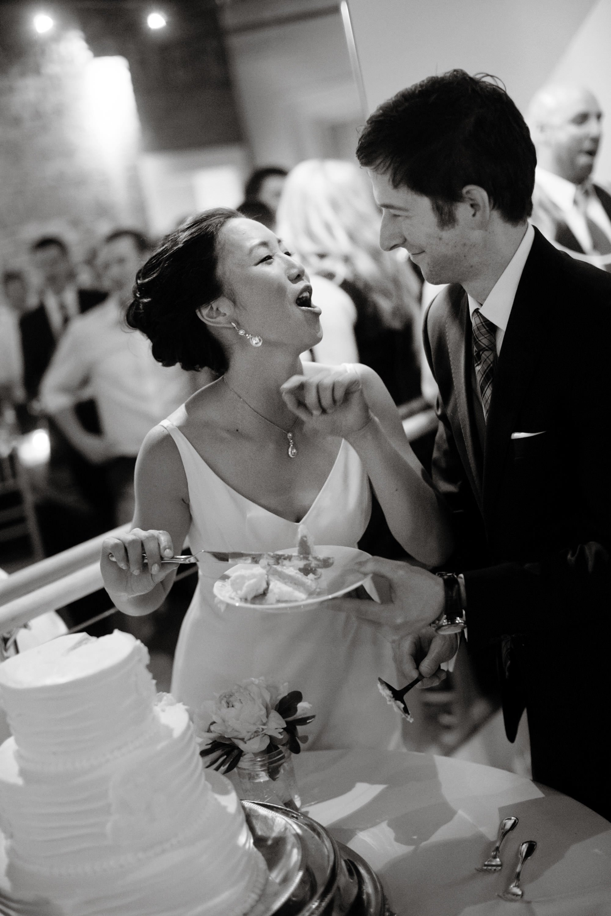 The bride and groom cut the cake during their Epic Yoga Studio wedding.