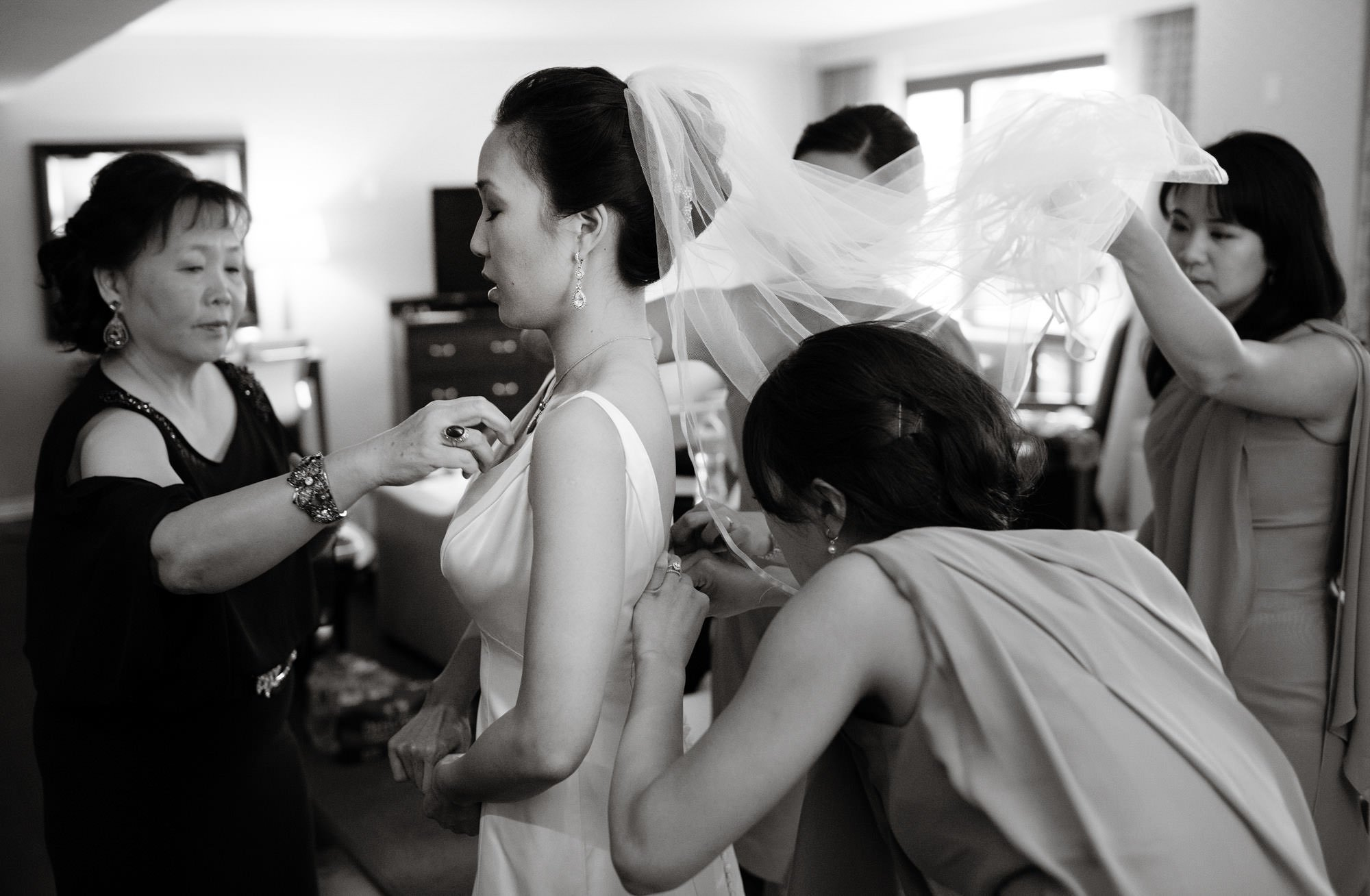 Bridesmaids help the bride put on her wedding dress before her Epic Yoga Studio wedding.