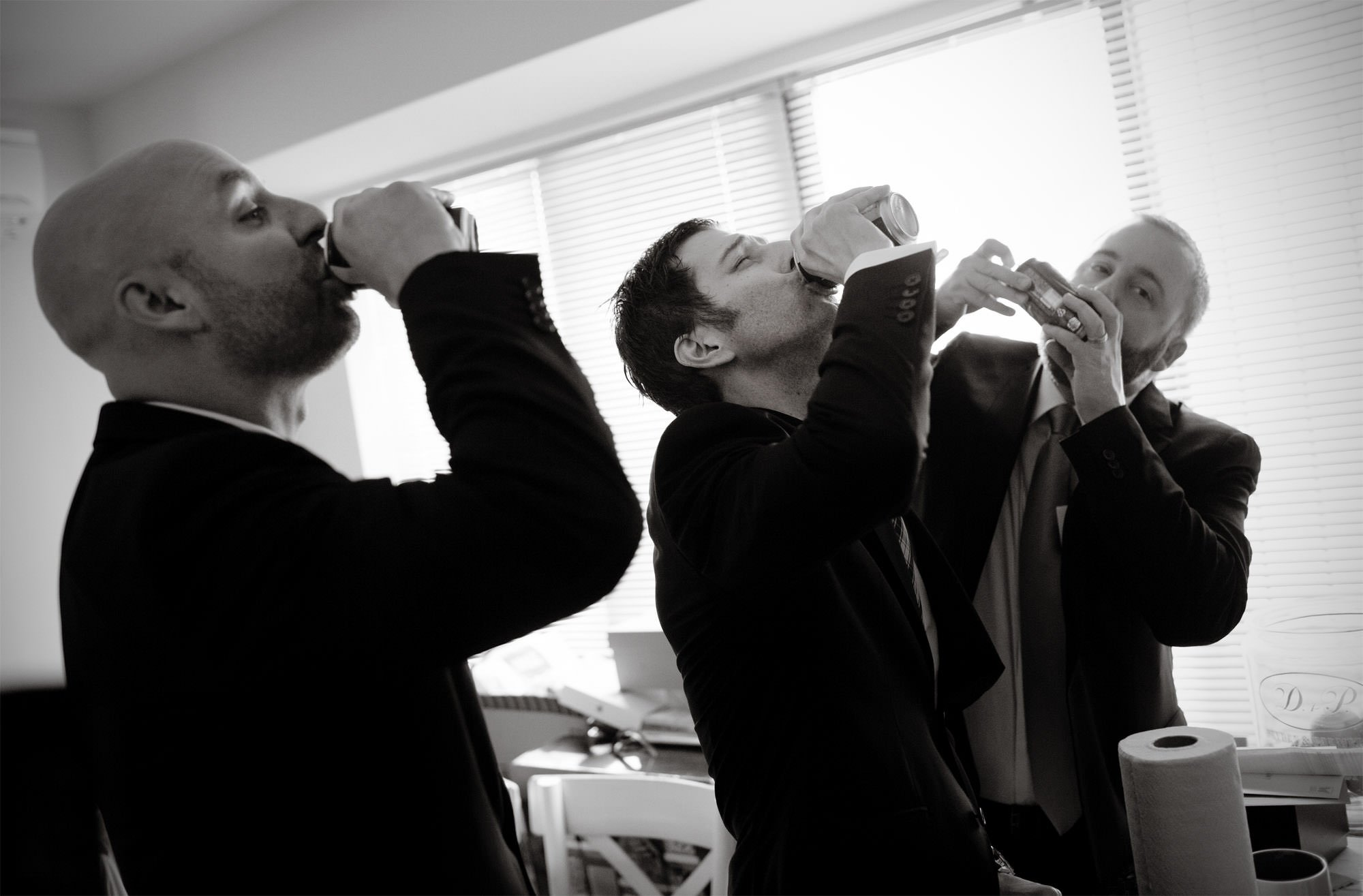 Groomsmen drink beers while getting ready before the Epic Yoga Studio wedding.