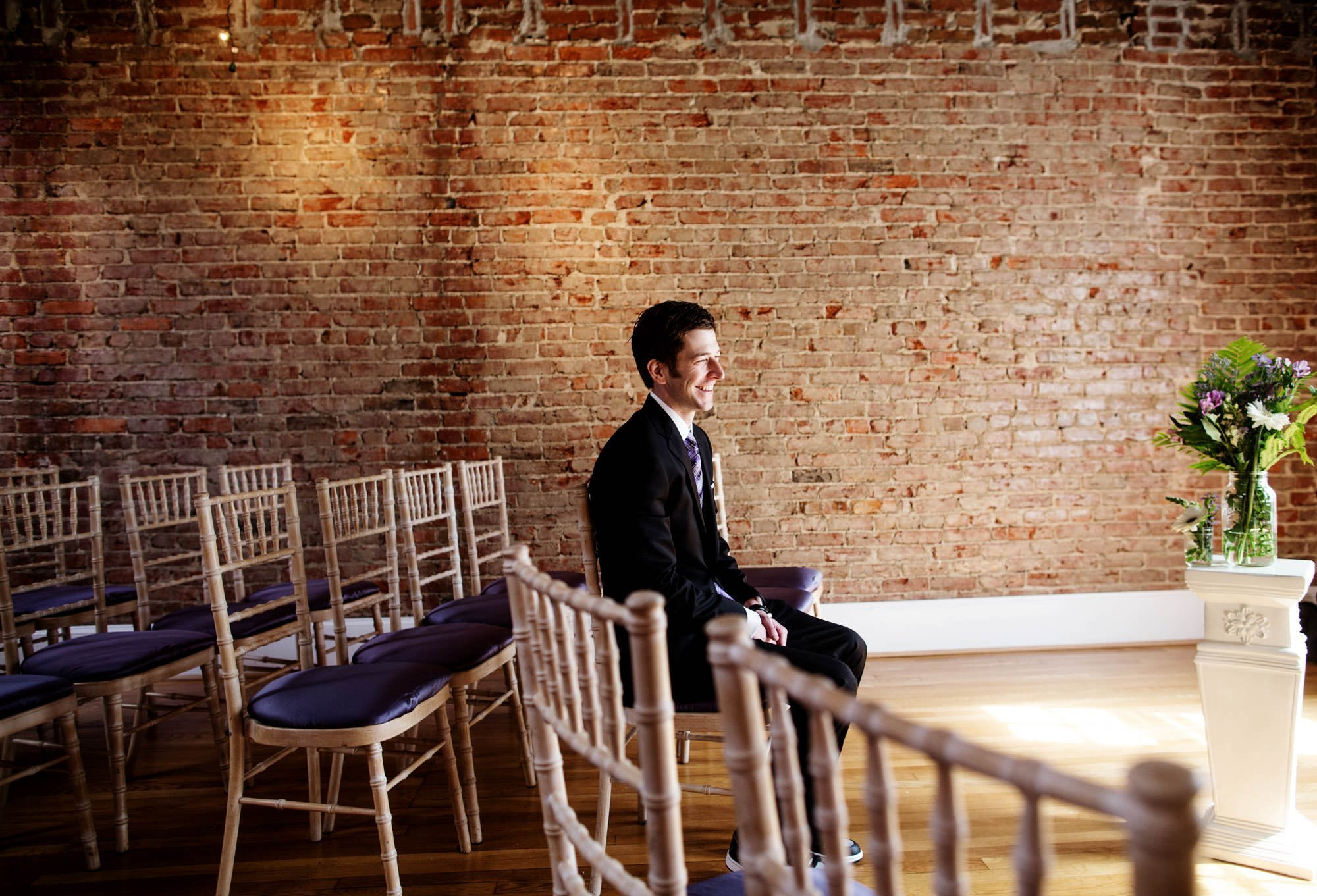 The groom waits for his bride before his Epic Yoga Studio wedding.