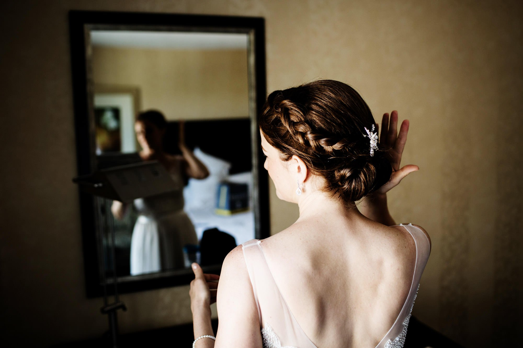 The bride fixes her hair in the mirror.