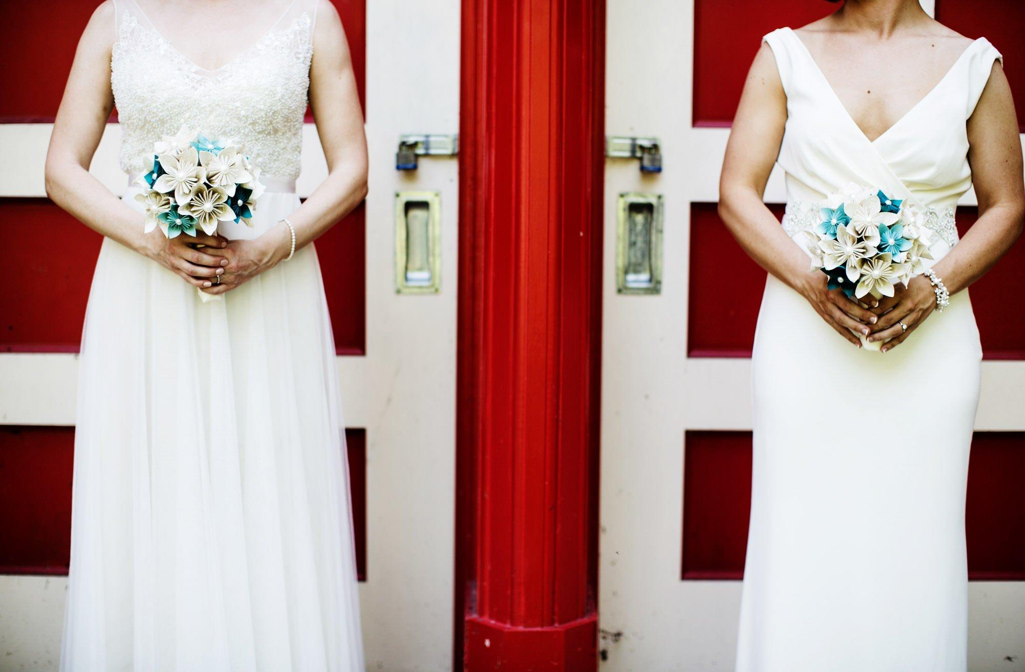The brides show off their DIY bouquets at their Glen Echo Park wedding.