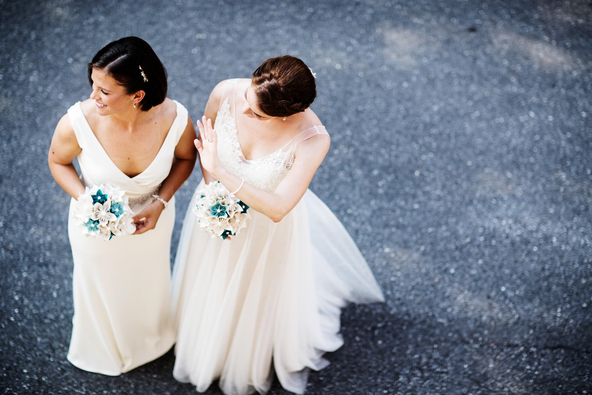 The brides wave to their guests.