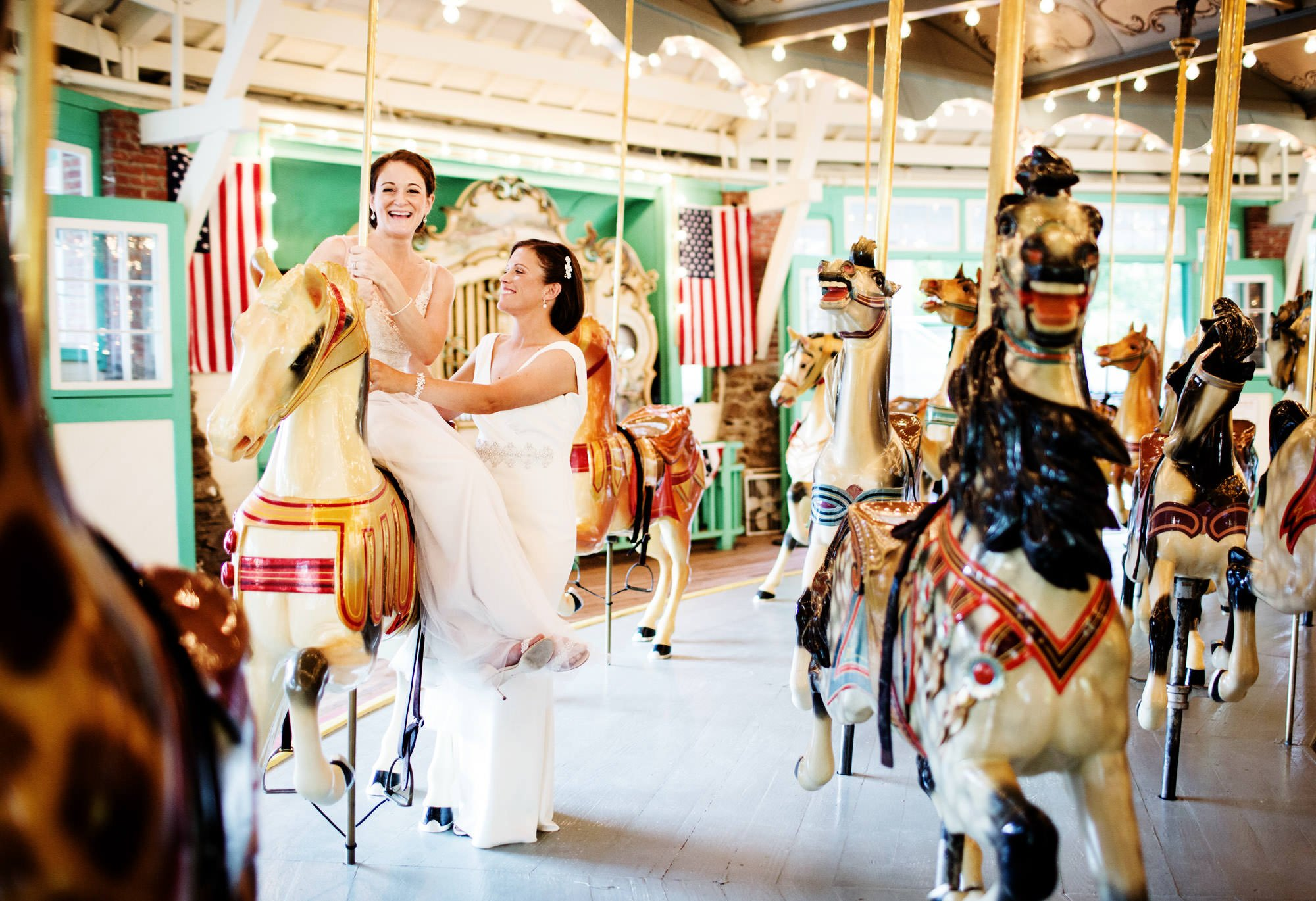 Glen Echo Park Wedding in Washington, DC  I  The two brides ride the Dentzel Carousel after their wedding ceremony.