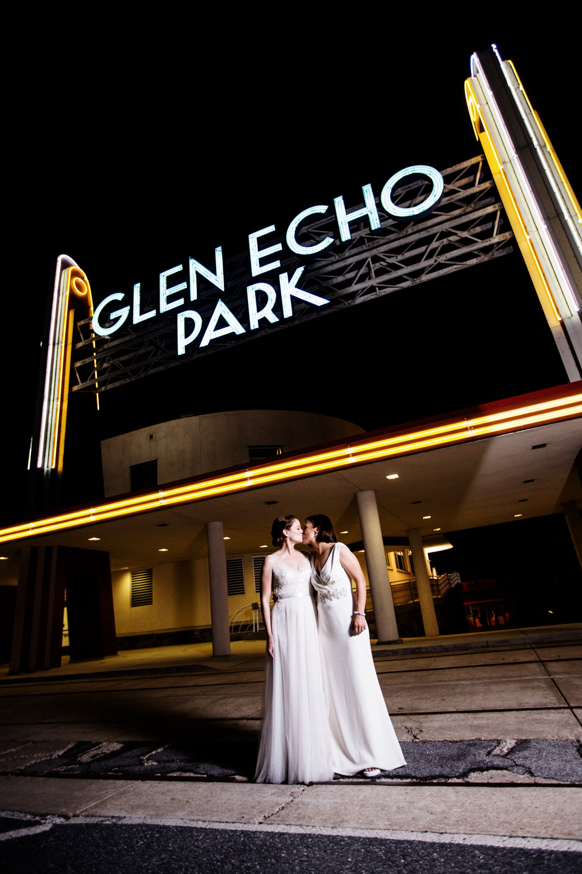 The brides pose for a portrait in front of Glen Echo Park in Washington, DC.