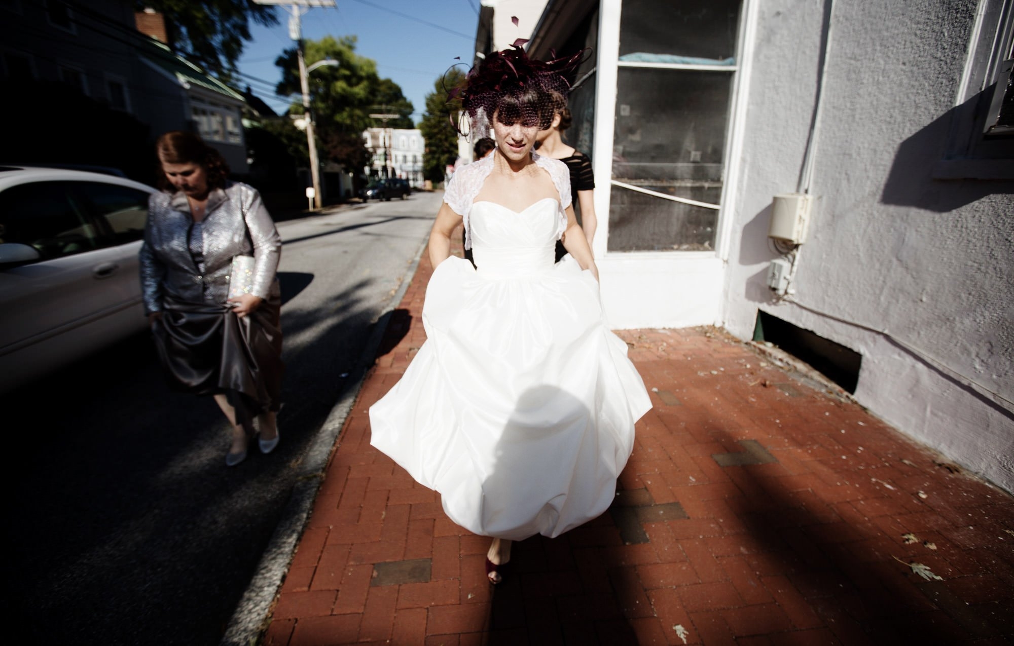 The bride walks down the street in Annapolis, MD.