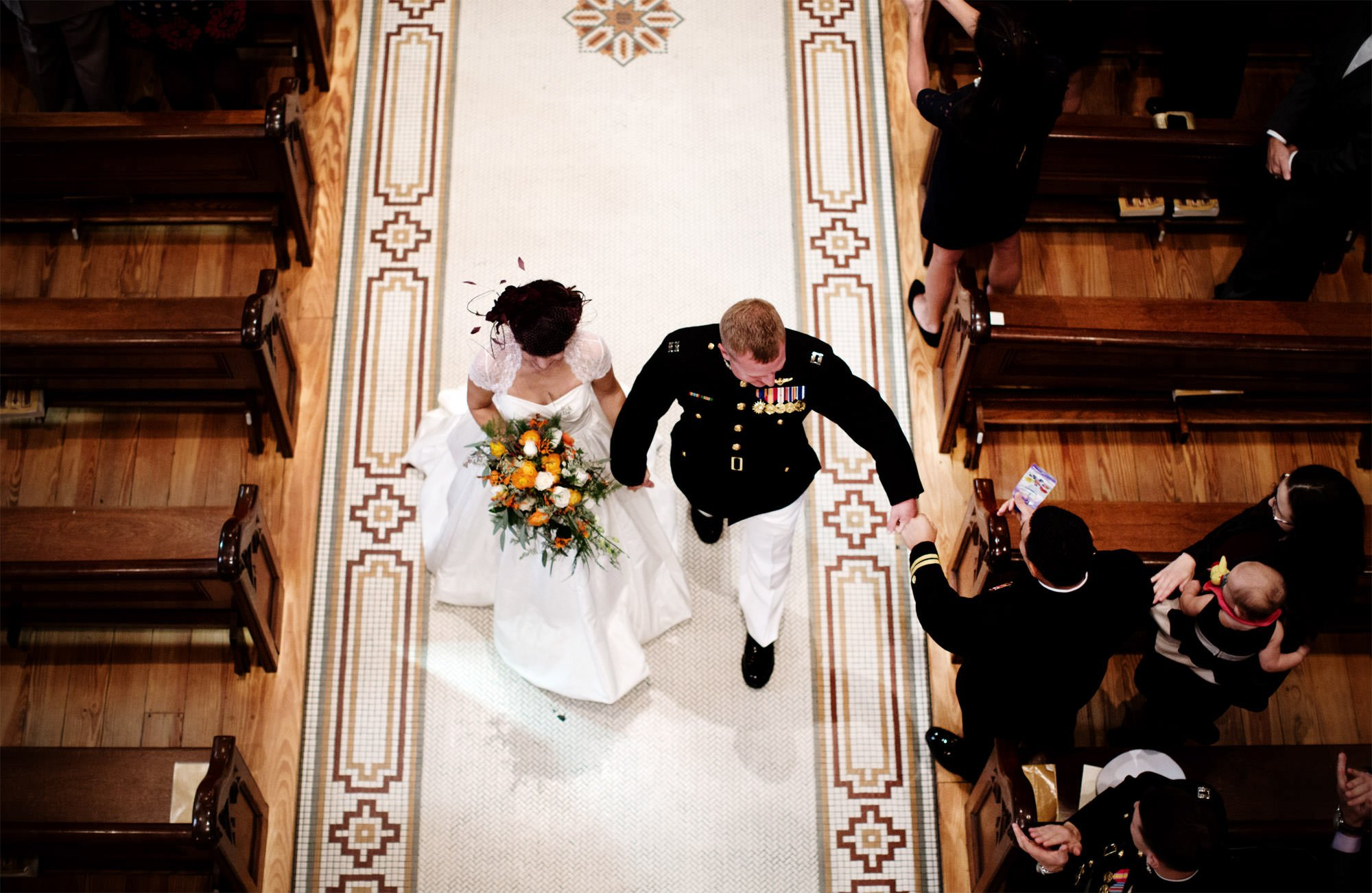 The bride and groom walk down the aisle following their wedding ceremony at St. Mary's Catholic Church.