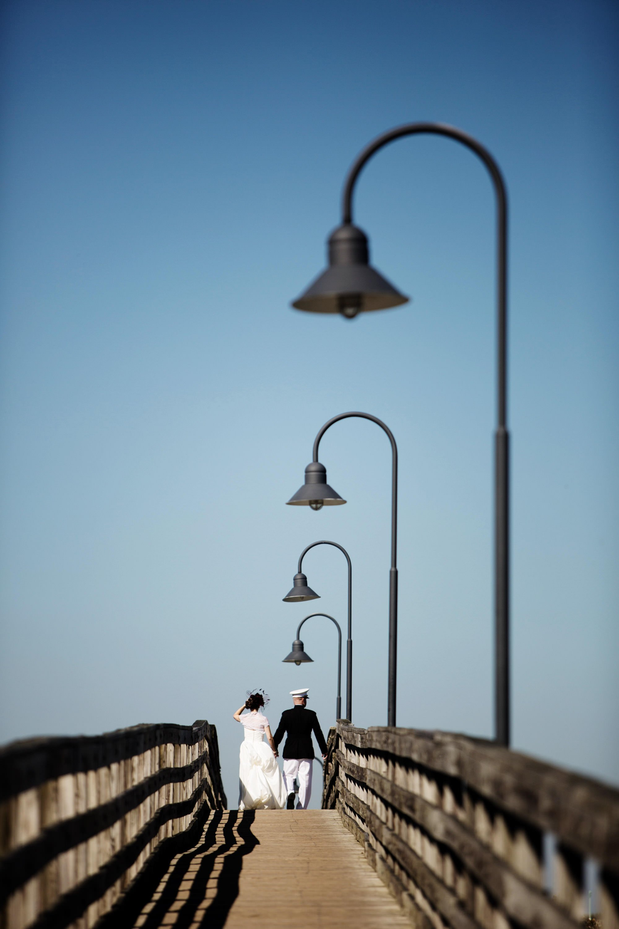 The bride and groom walk down a boardwalk at the Annapolis Naval Academy.