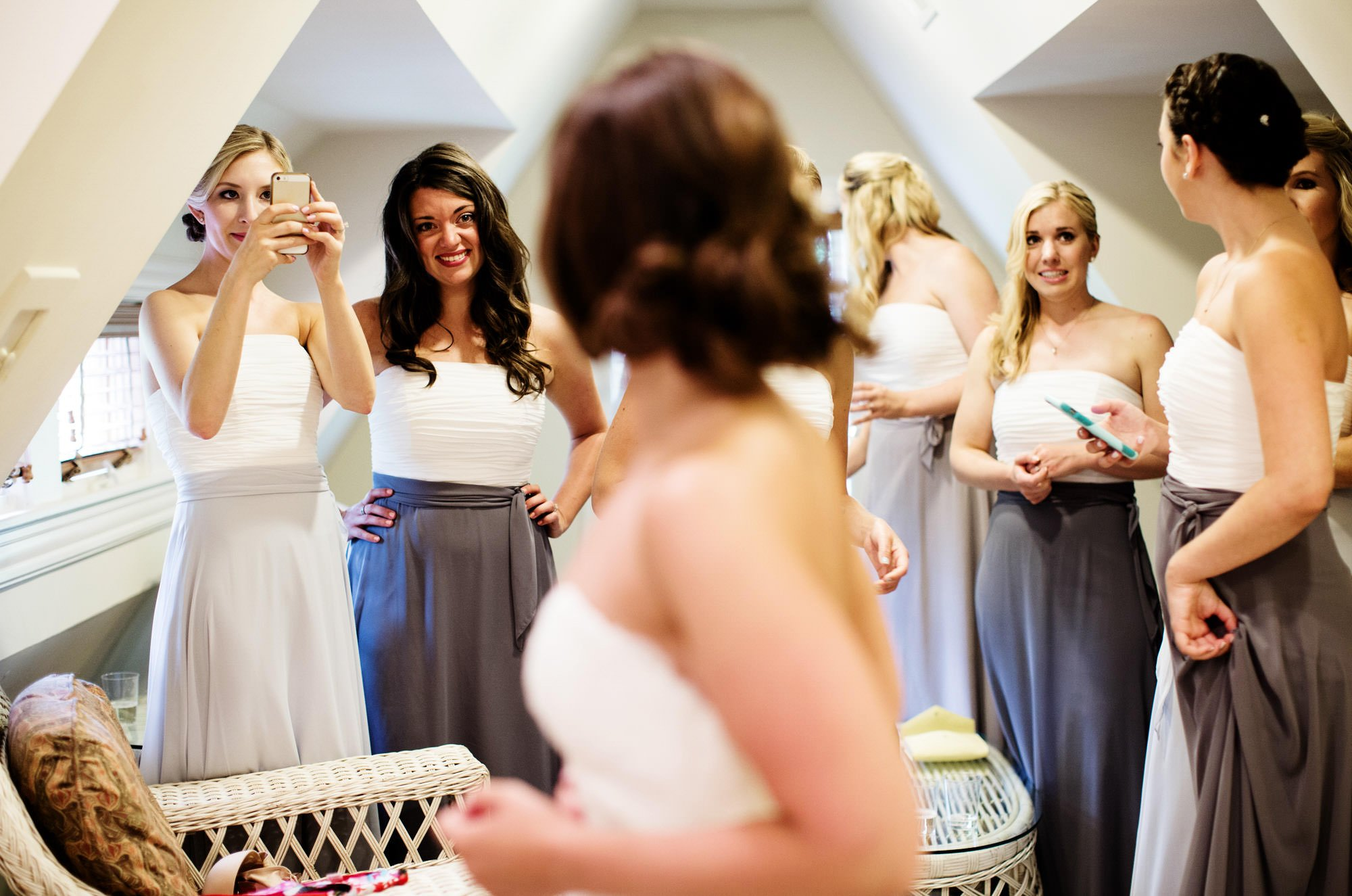 The bride puts on her wedding dress as her bridesmaids look on.