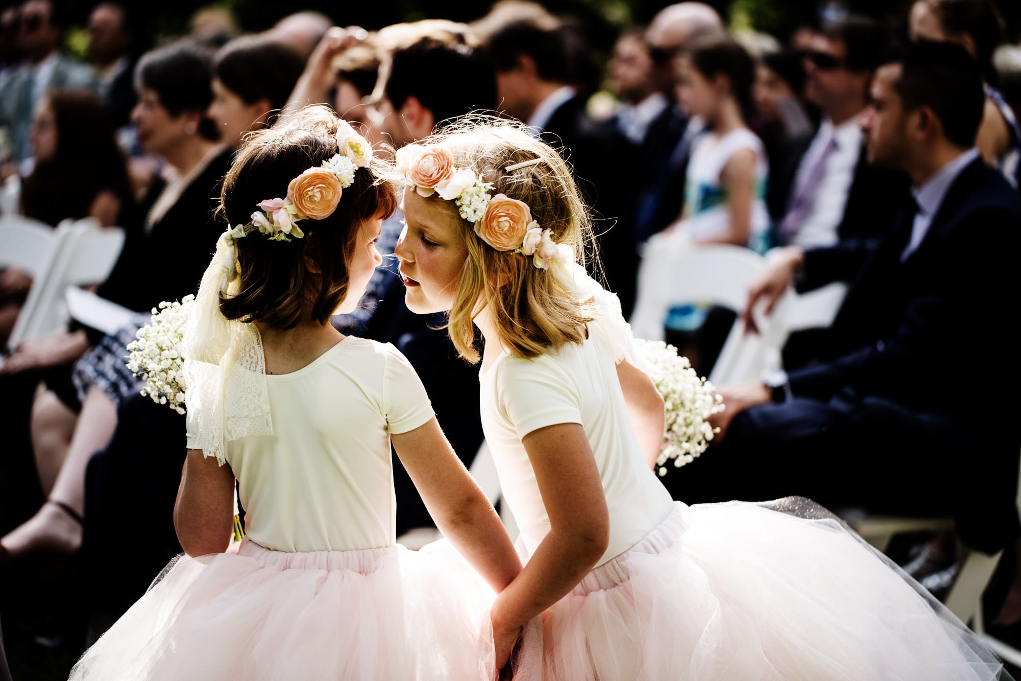 Flower girls whisper to each other while the couple gets married.