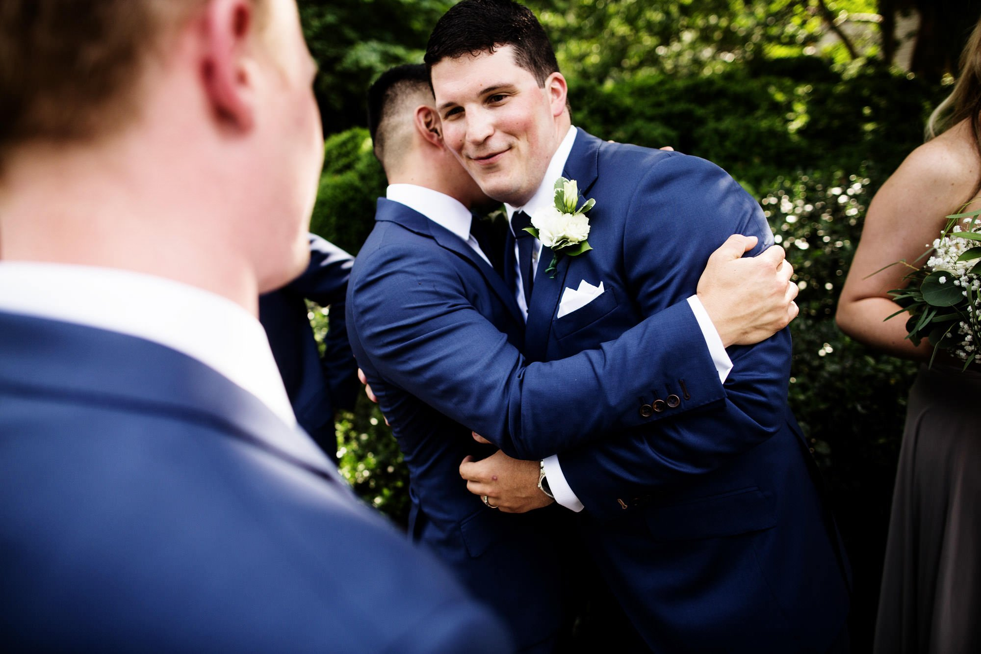 The groom is hugged by friends following the ceremony.