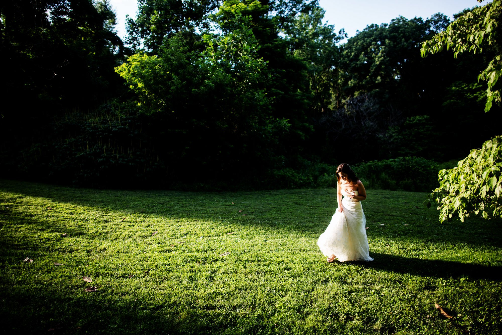 The bride stands in a field of grass following the ceremony.