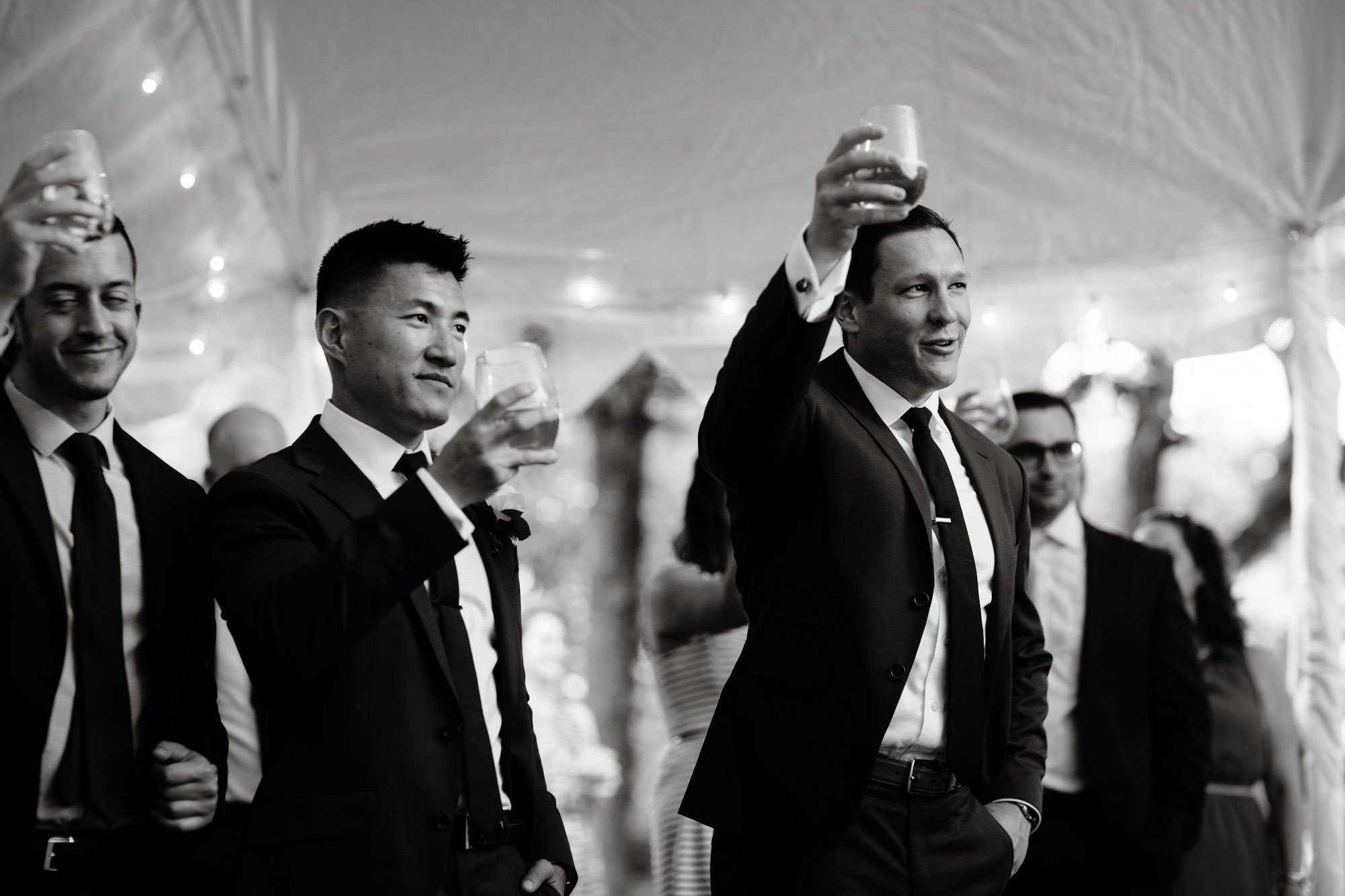 Groomsmen raise their glasses during a toast.