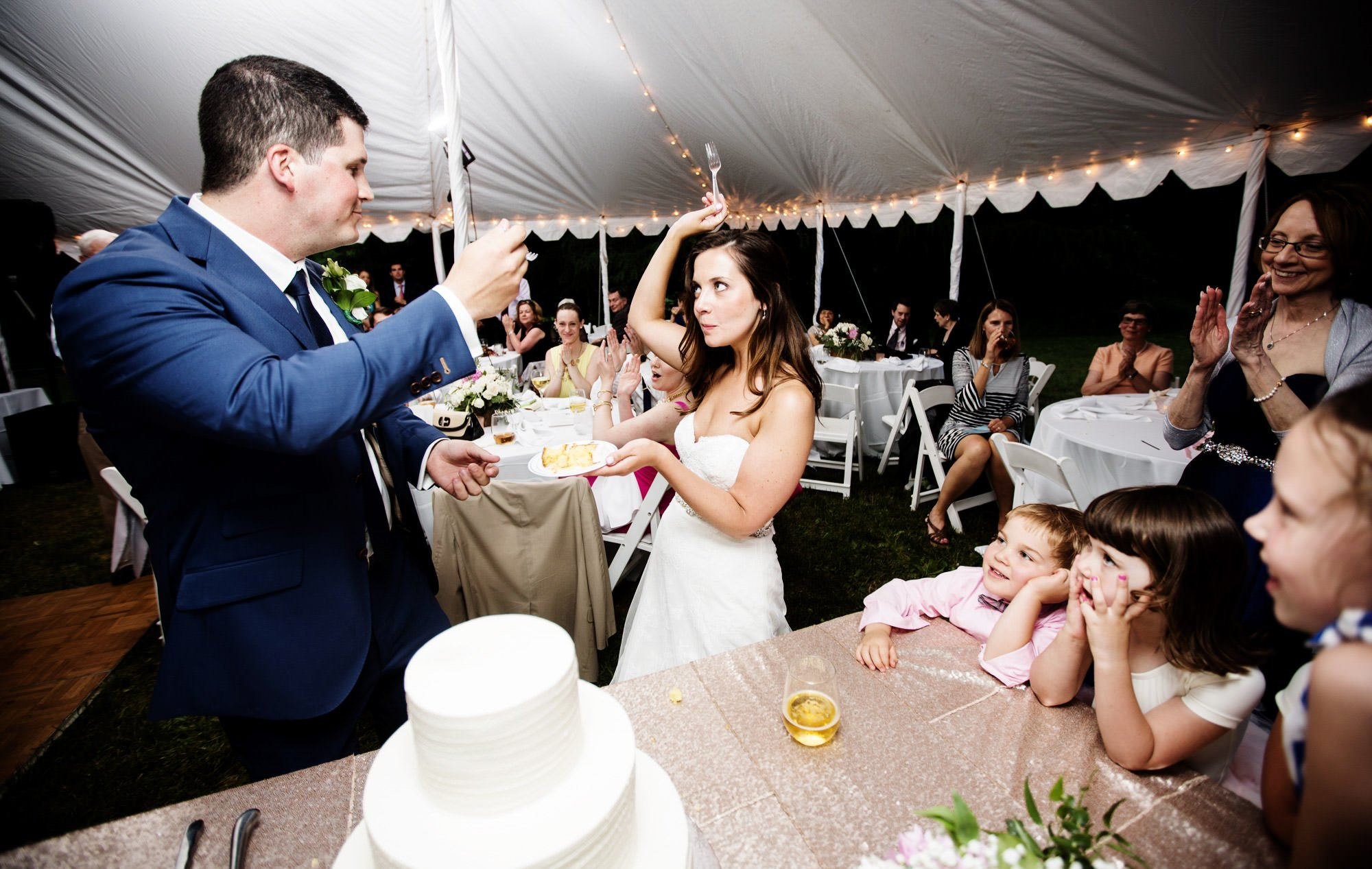 The bride and groom cut their cake during the wedding reception at Hendry House.