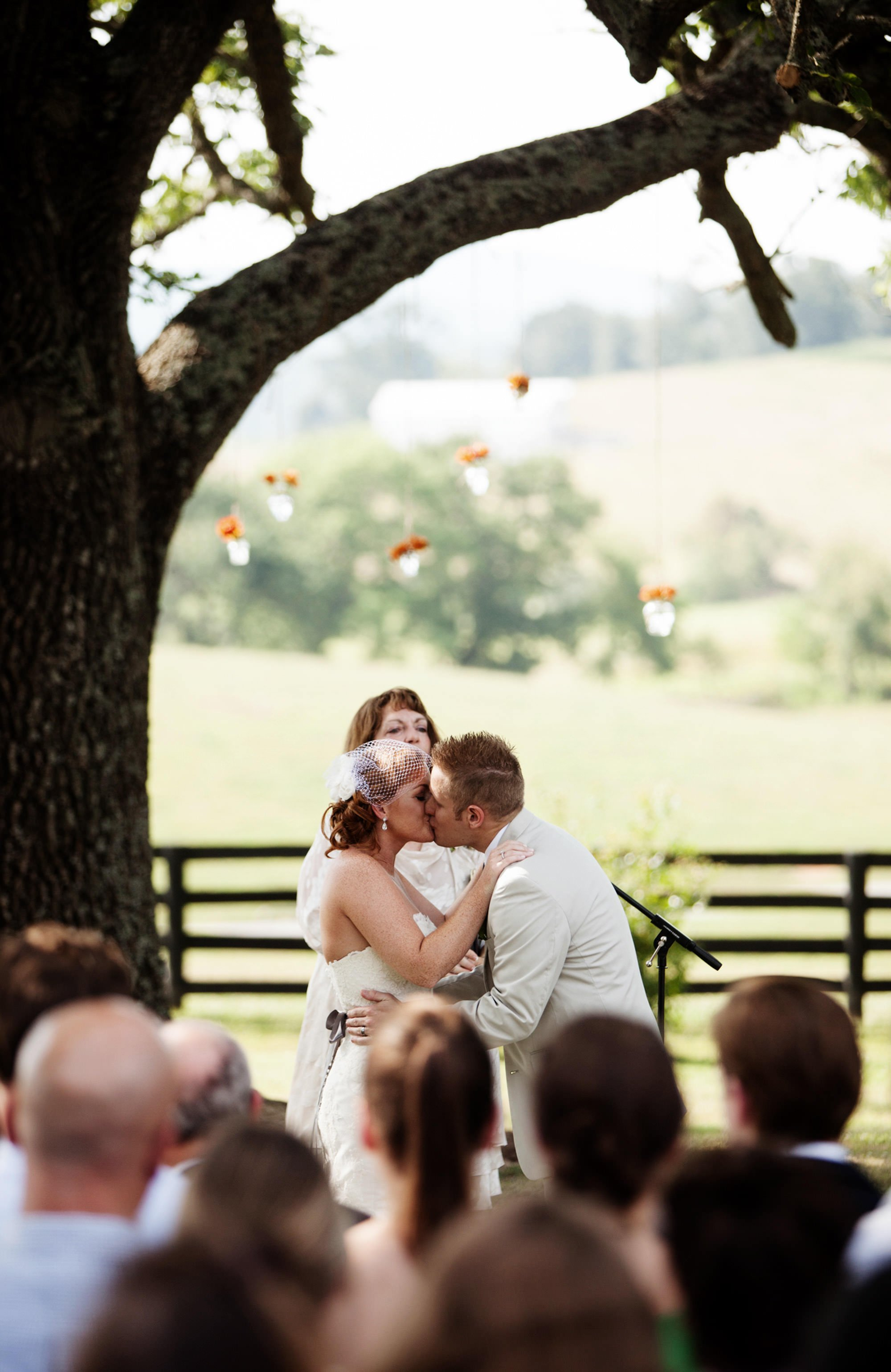 The bride and groom share their first kiss under a tree during their Marriott Ranch wedding.