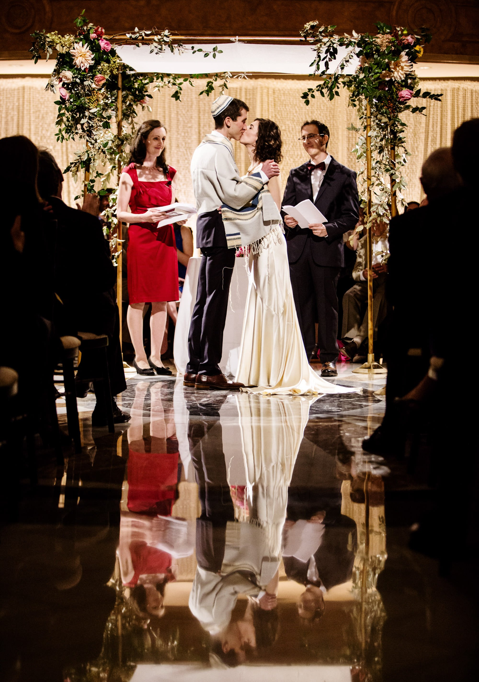 The bride and groom share their first kiss under the chuppah during their wedding ceremony.